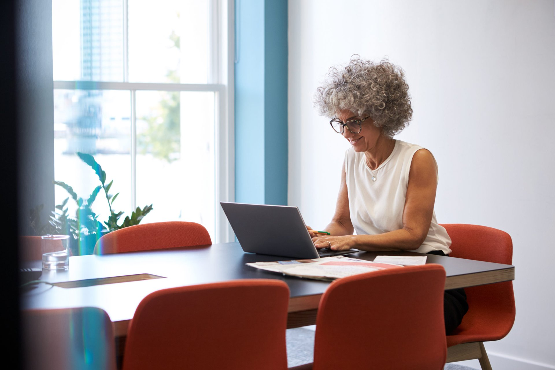 An older woman working on a laptop