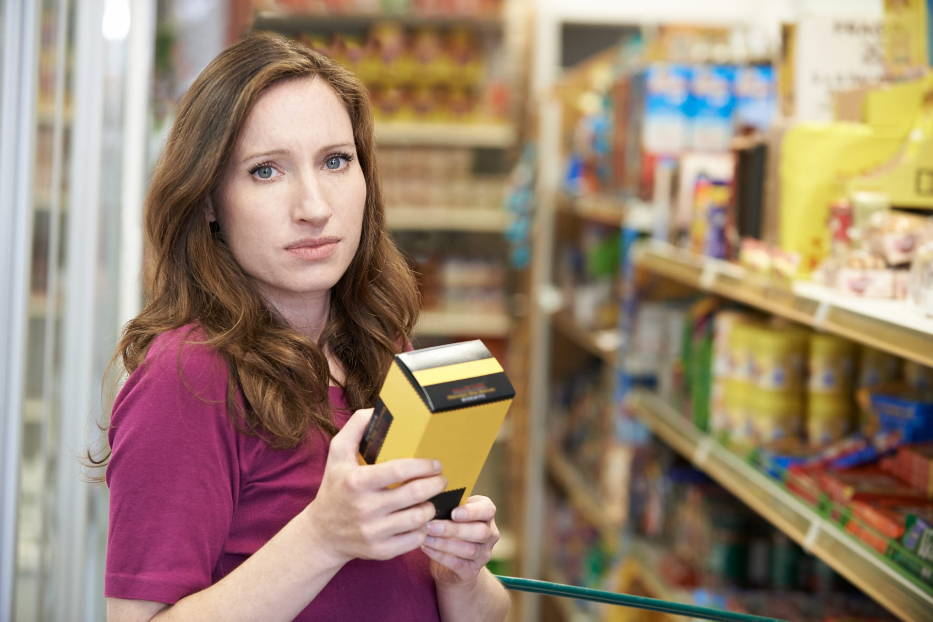 Woman checking label in grocery store