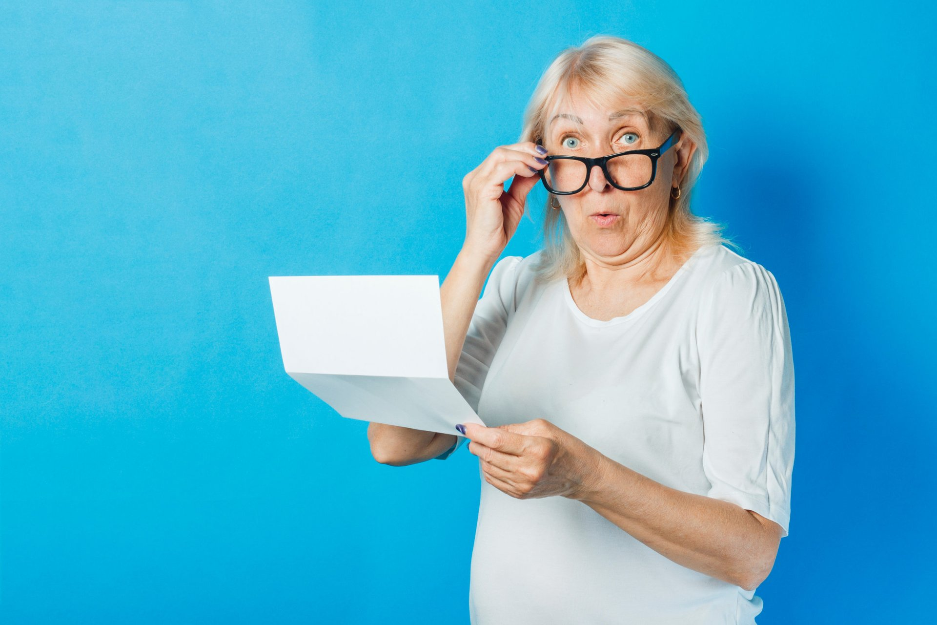 An older woman lowers her eyeglasses in surprise while holding a document