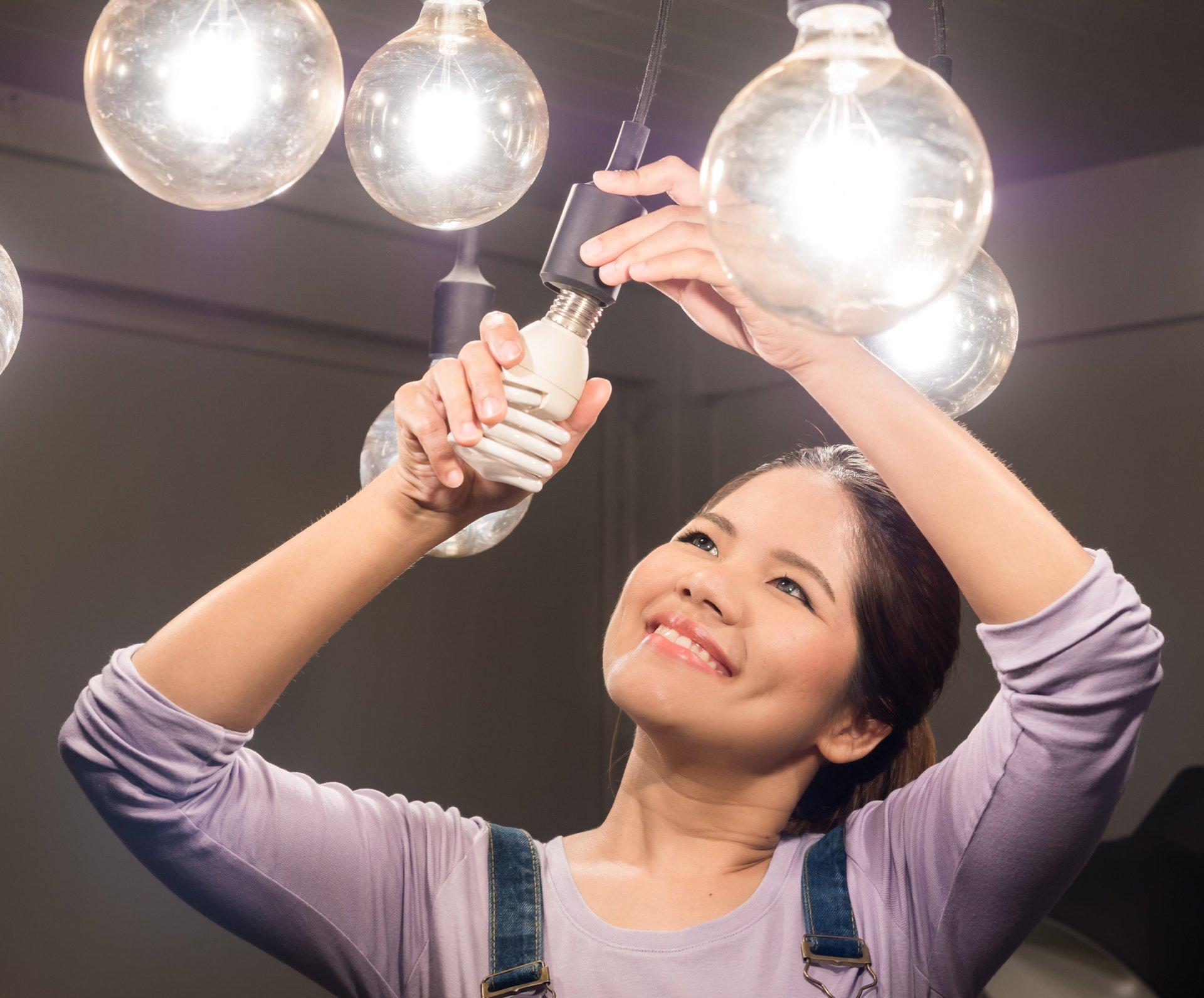 Woman changing lightbulbs