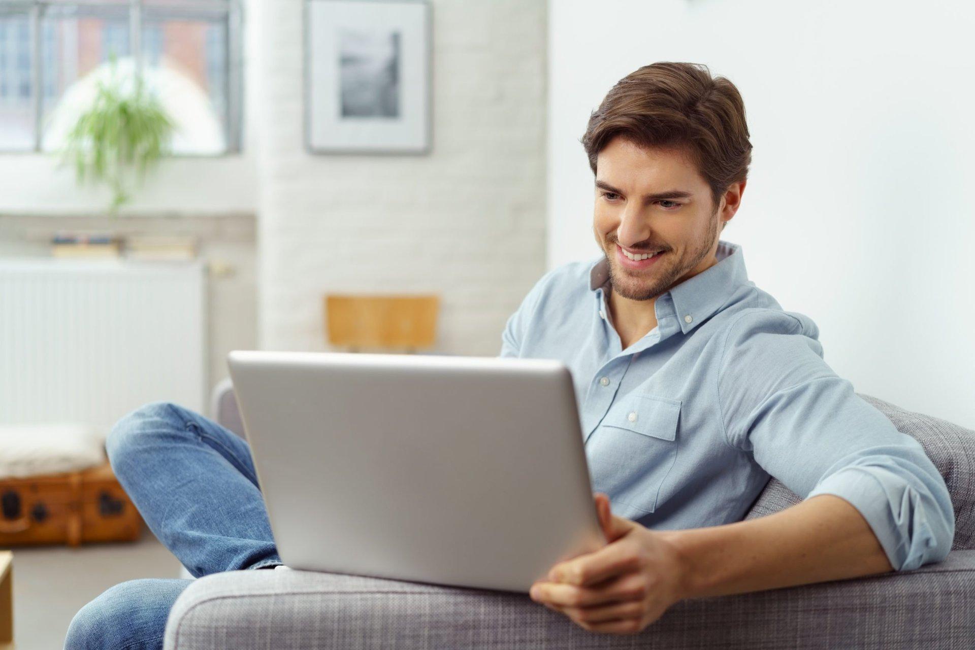 Man happily using laptop