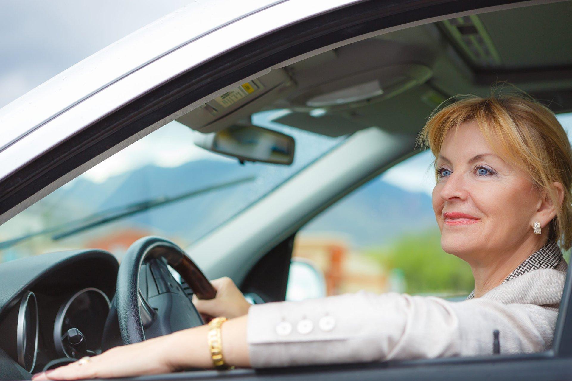 an older woman drives a car
