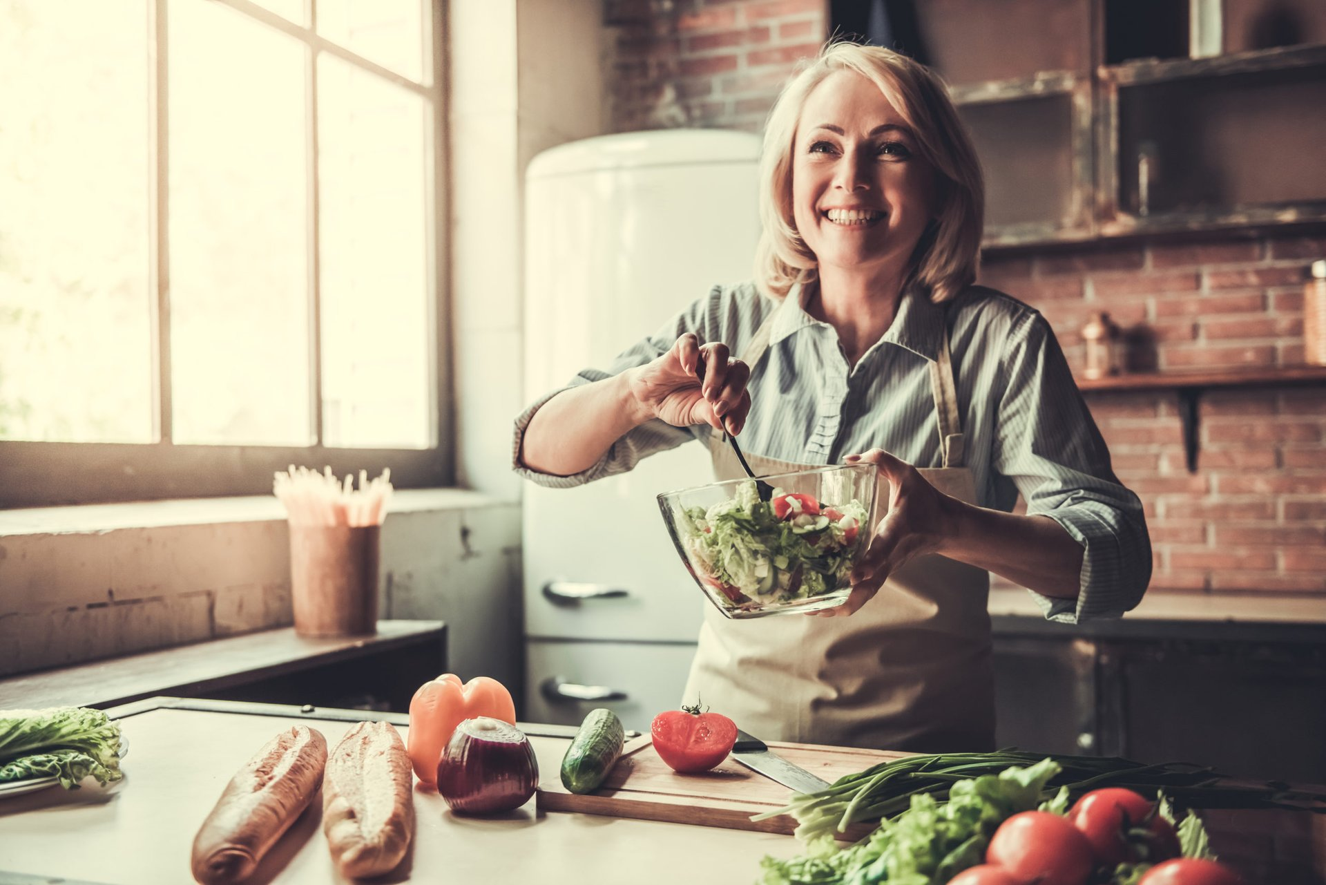 A woman makes a salad in her kitchen