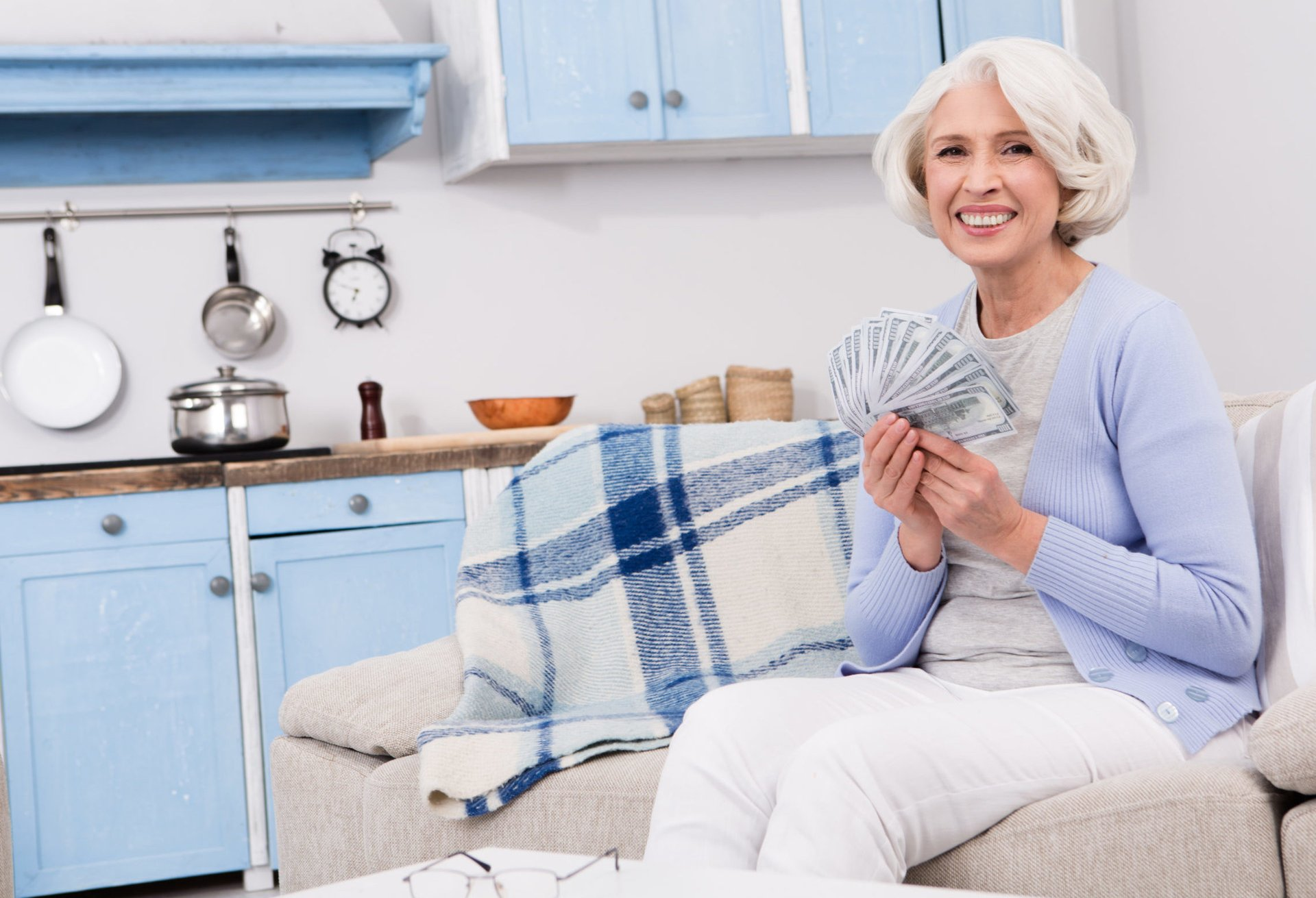 A senior holds a fan of $100 bills while sitting on her sofa