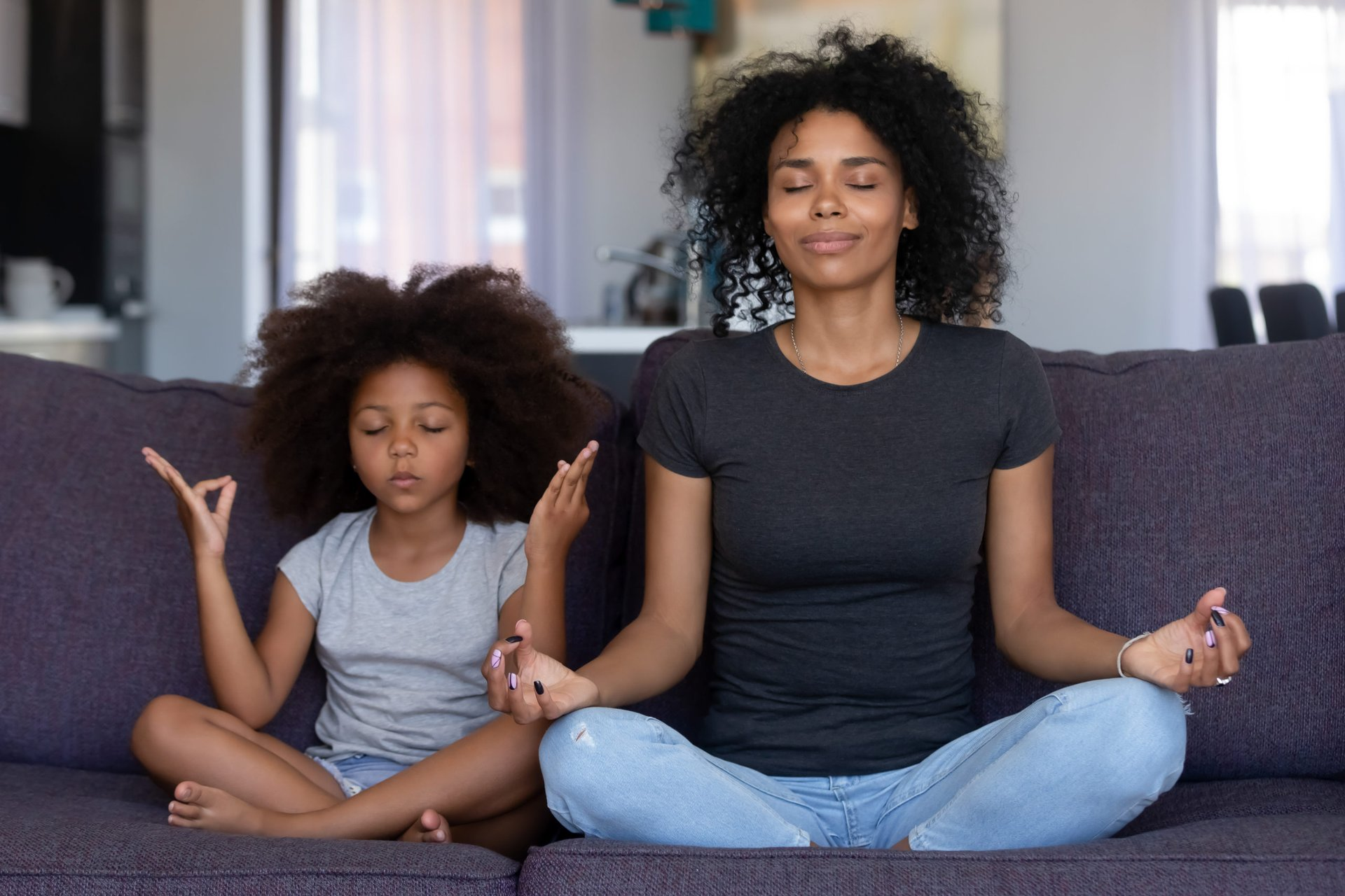 A mother and daughter meditating on a couch