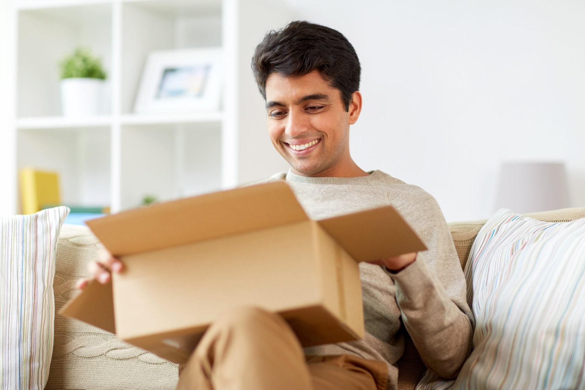 A happy man smiles while opening a package in a shipping box on his sofa