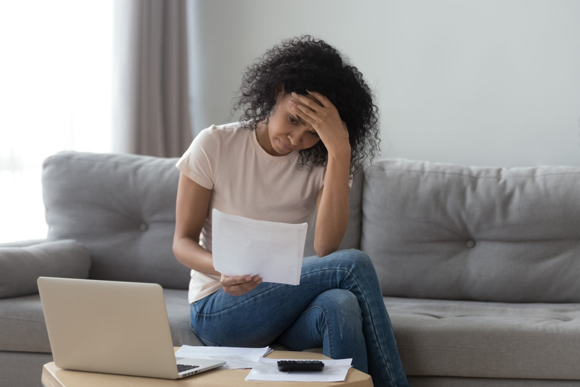 A stressed young woman worries about financial documents and bills over her laptop computer