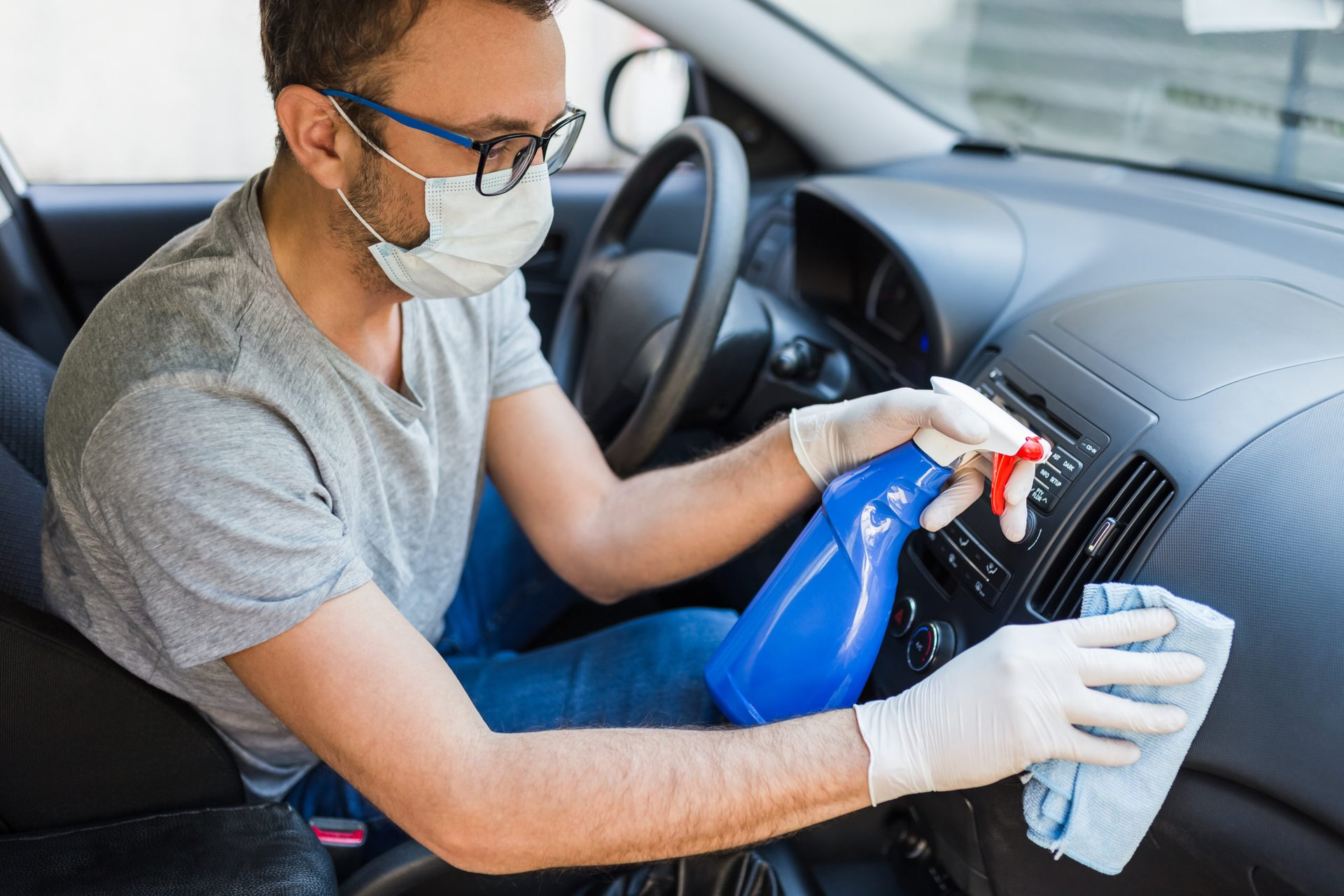 man in a mask cleaning coronavirus germs in his car