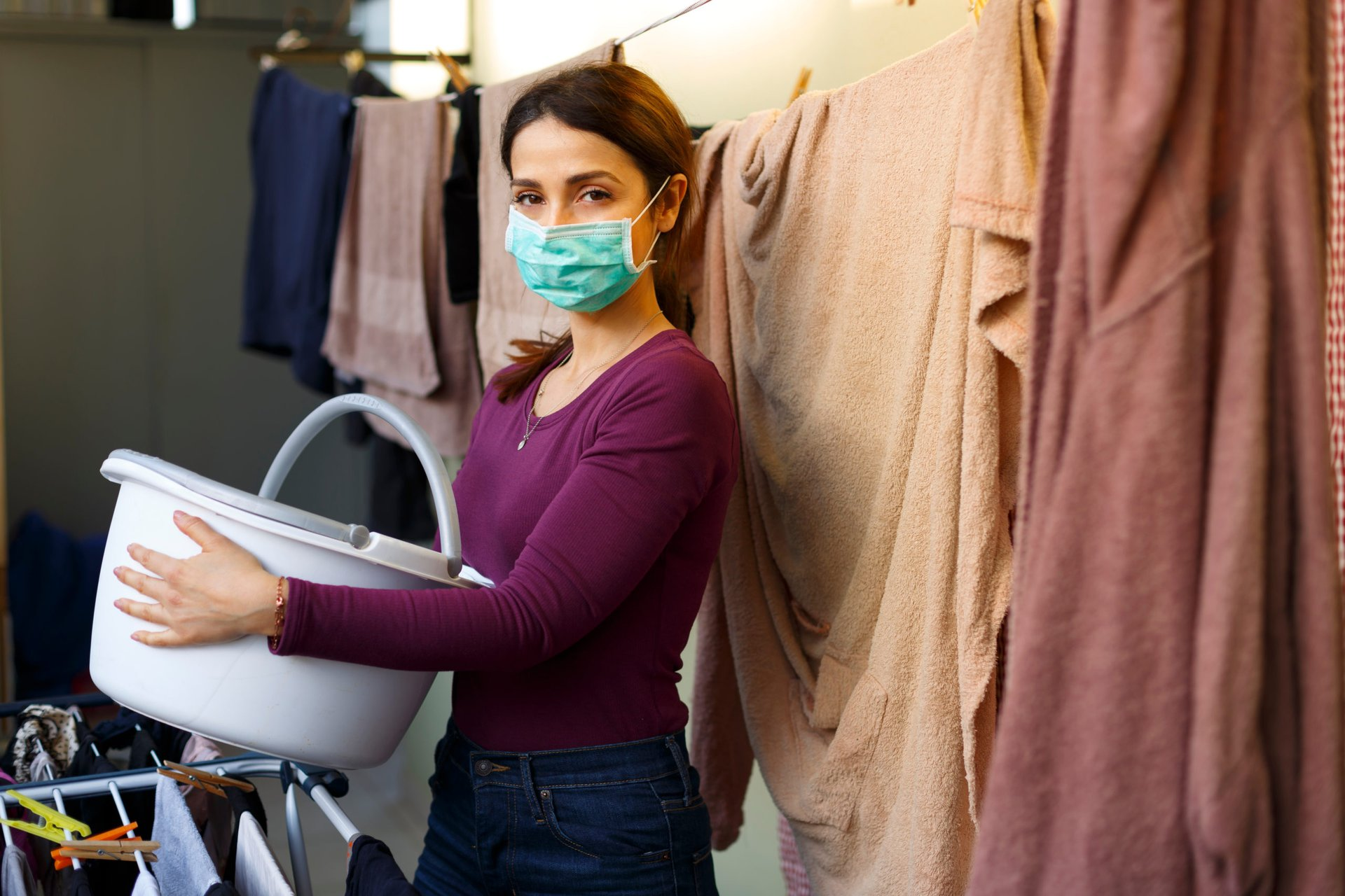 a woman does laundry in a mask
