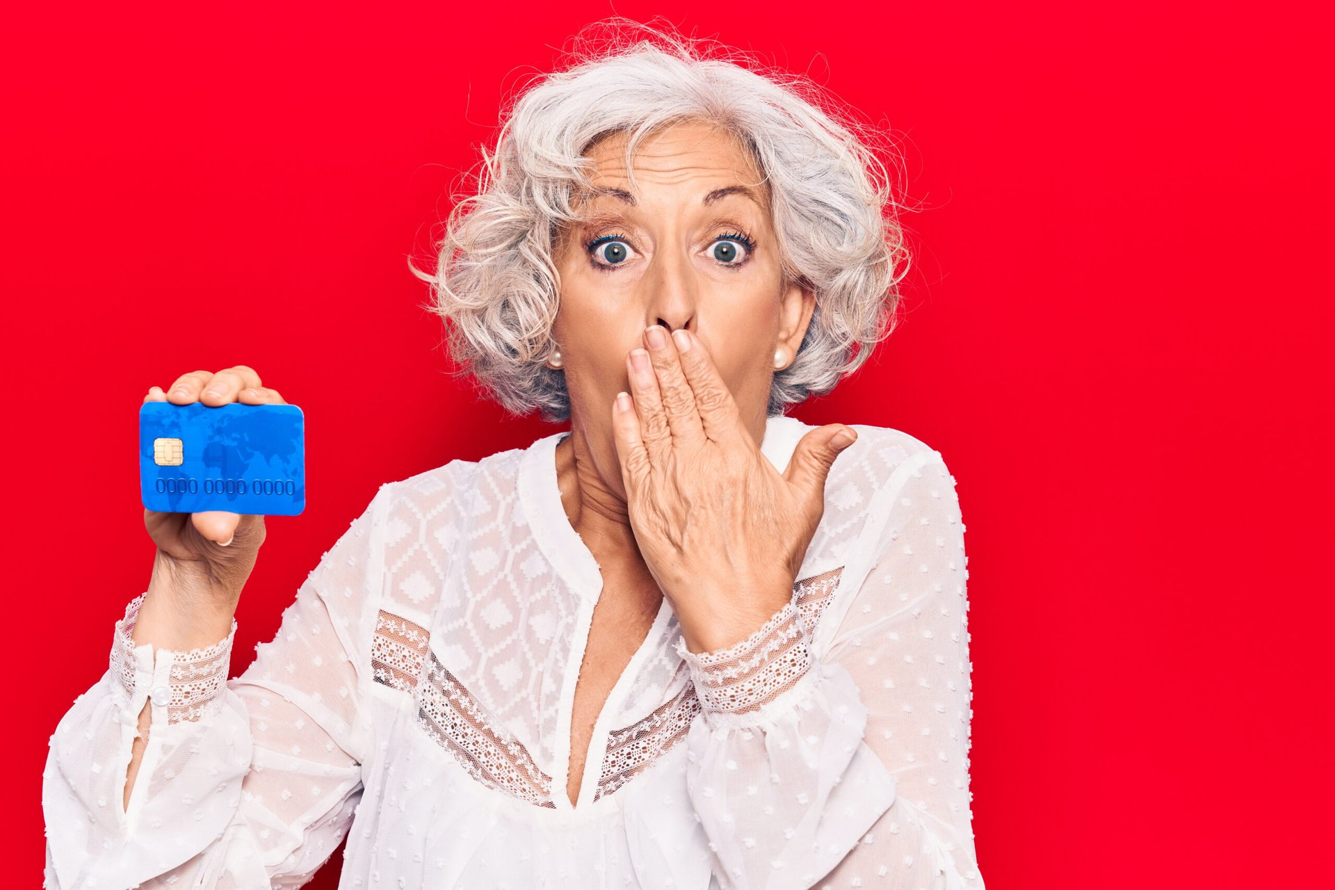 Surprised senior woman holding credit card