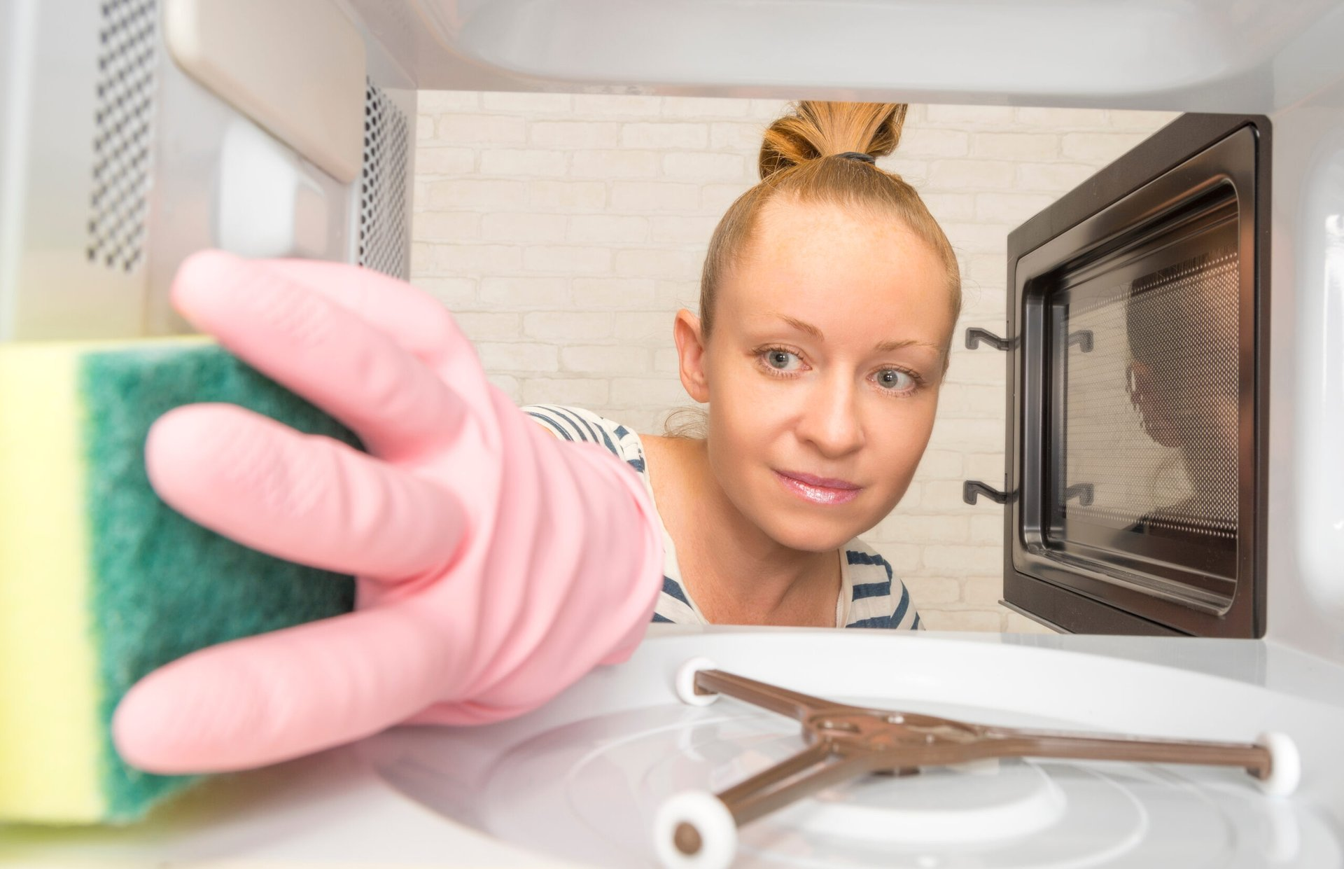 Woman cleans a microwave