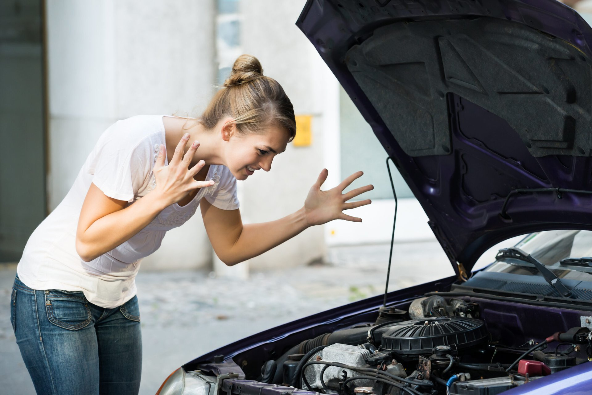 Frustrated woman with broken down car