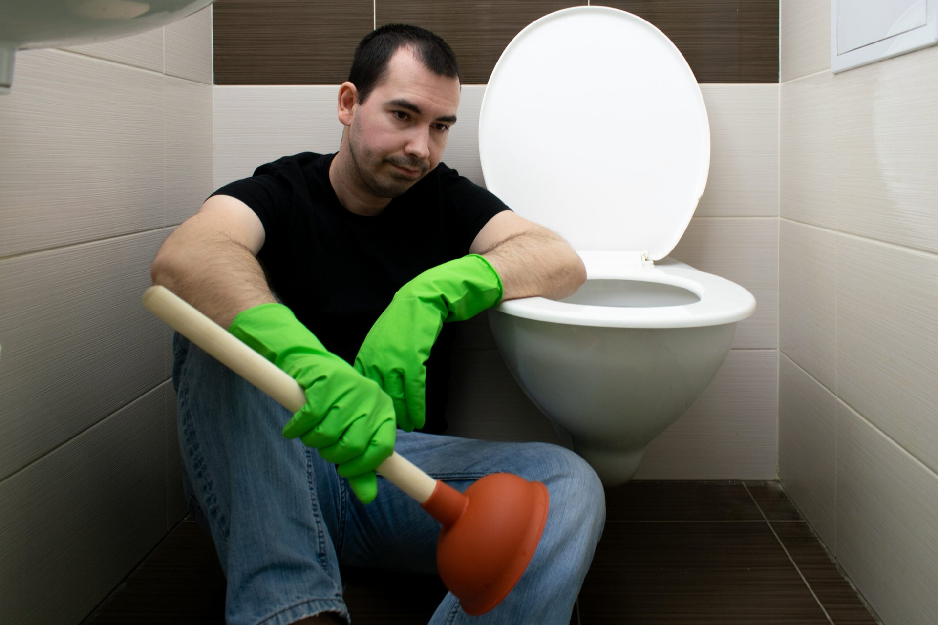 Man with plunger next to toilet