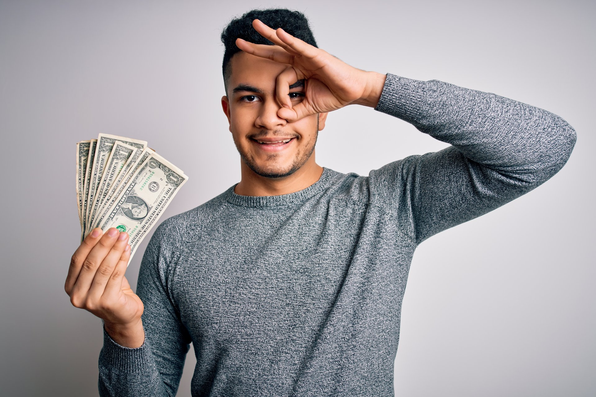 Man holding money and making OK sign