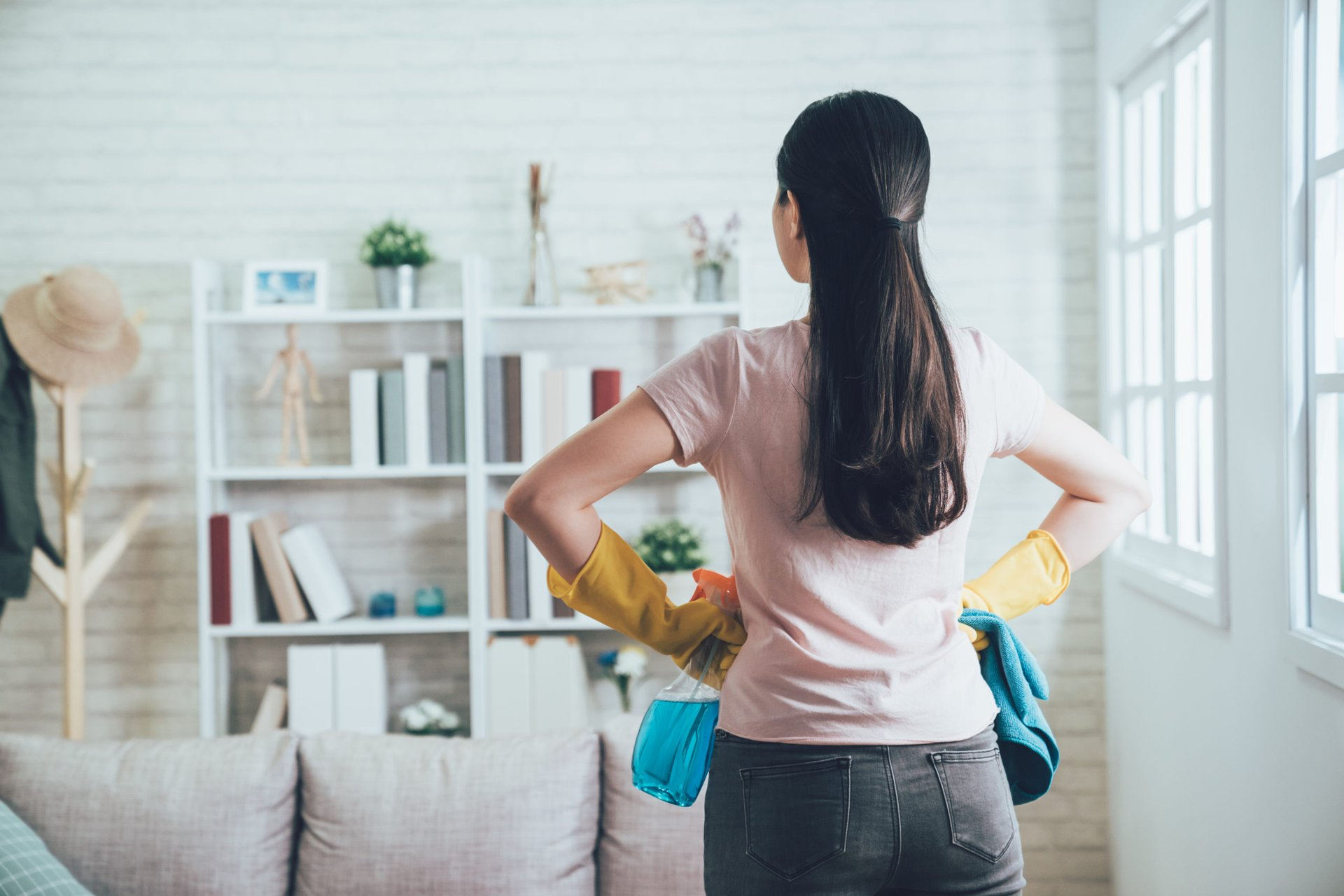 woman with cleaner bottle and gloves