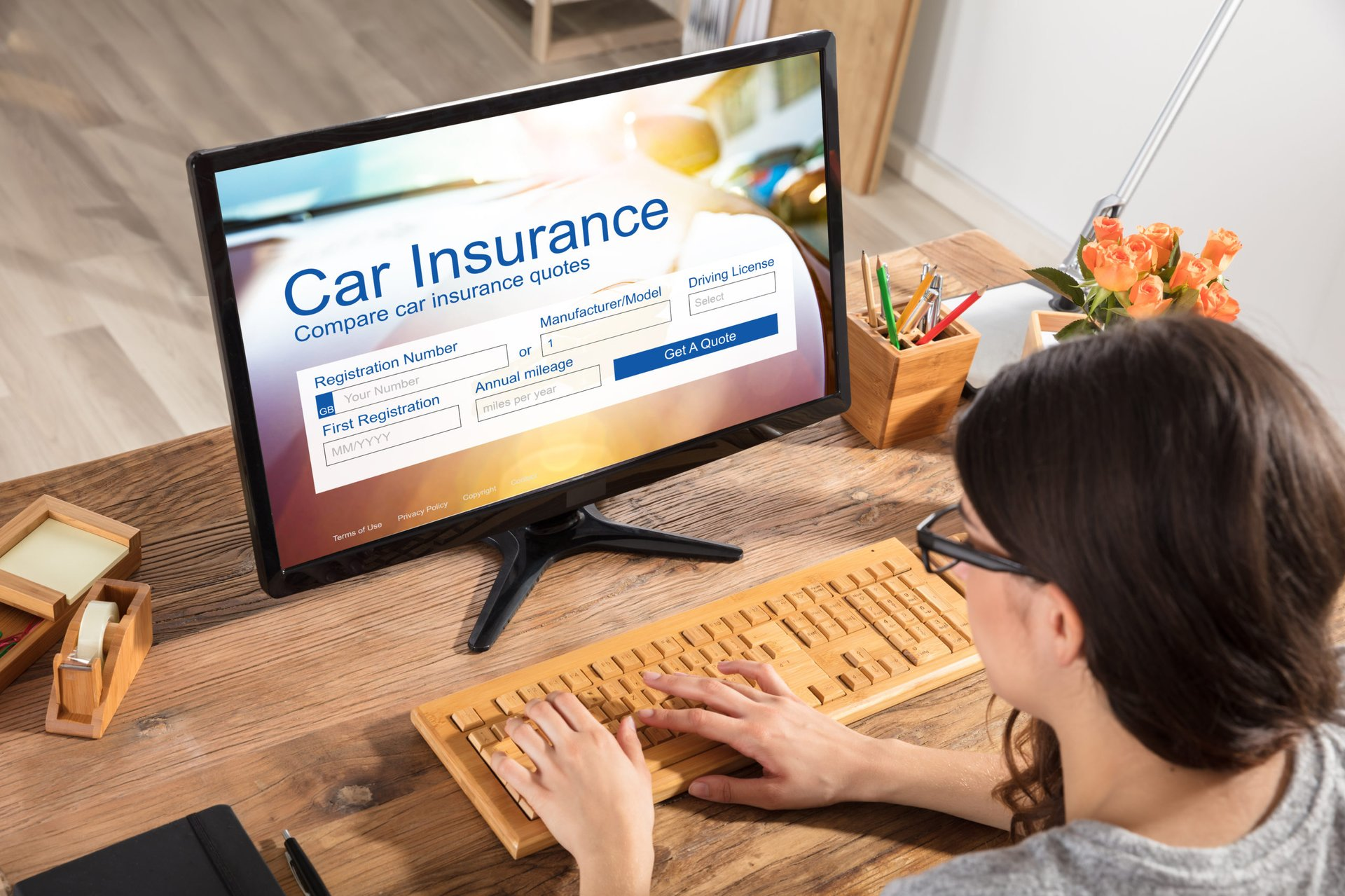 A young woman at her desktop computer searching for the best insurance companies for her car