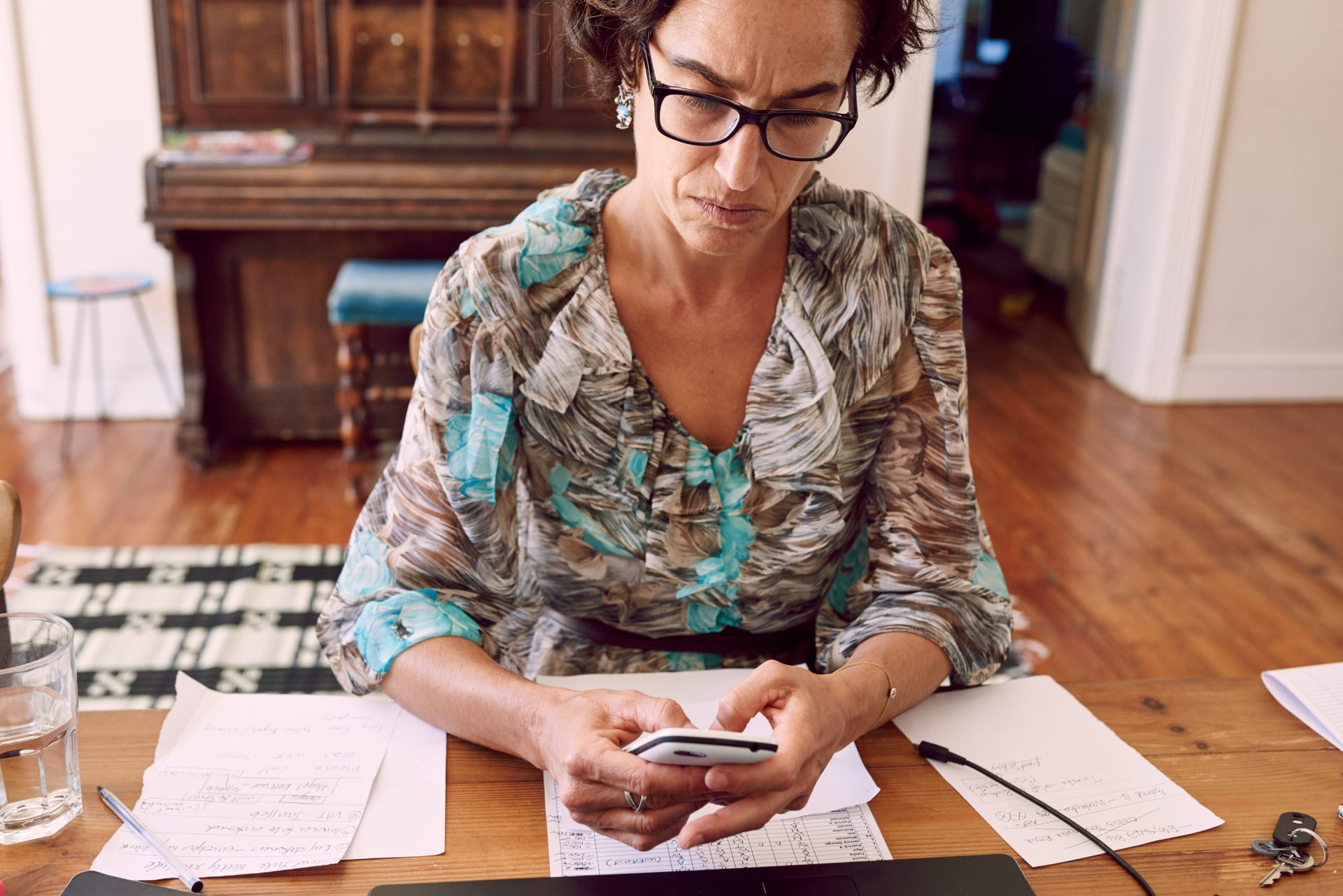 Older woman sitting at her desk comparing the best cell phone plans to save money
