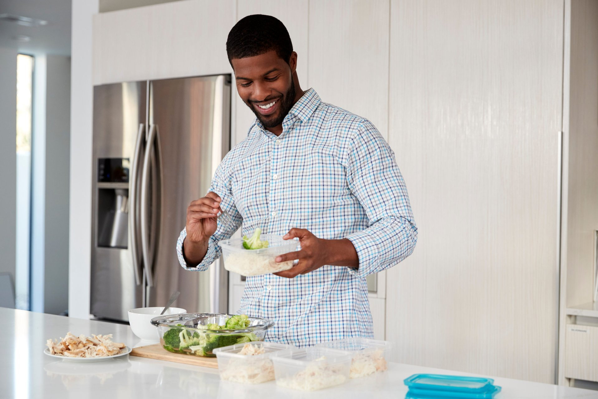 A man enjoying salad leftovers in the kitchen
