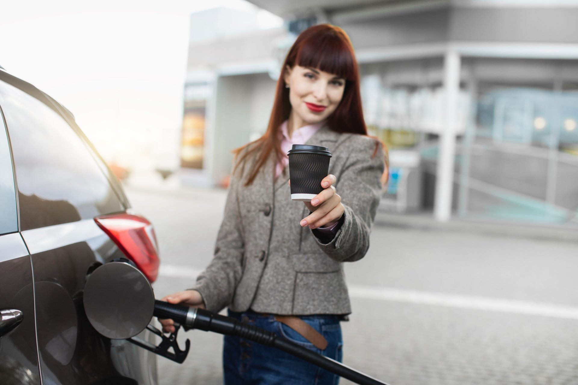 Woman holding coffee while pumping gas