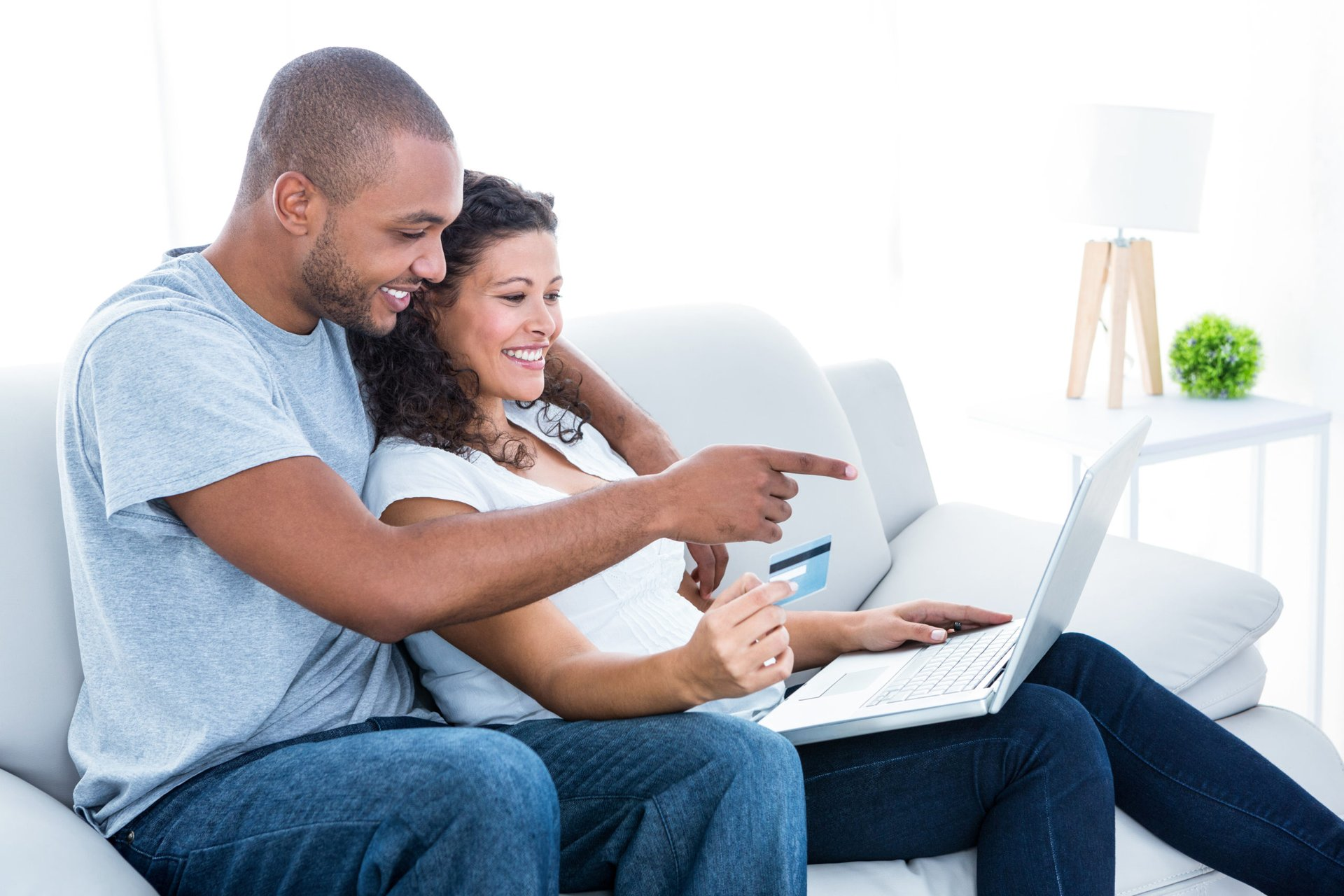 Couple on the couch with laptop and credit card spending their credit card rewards points