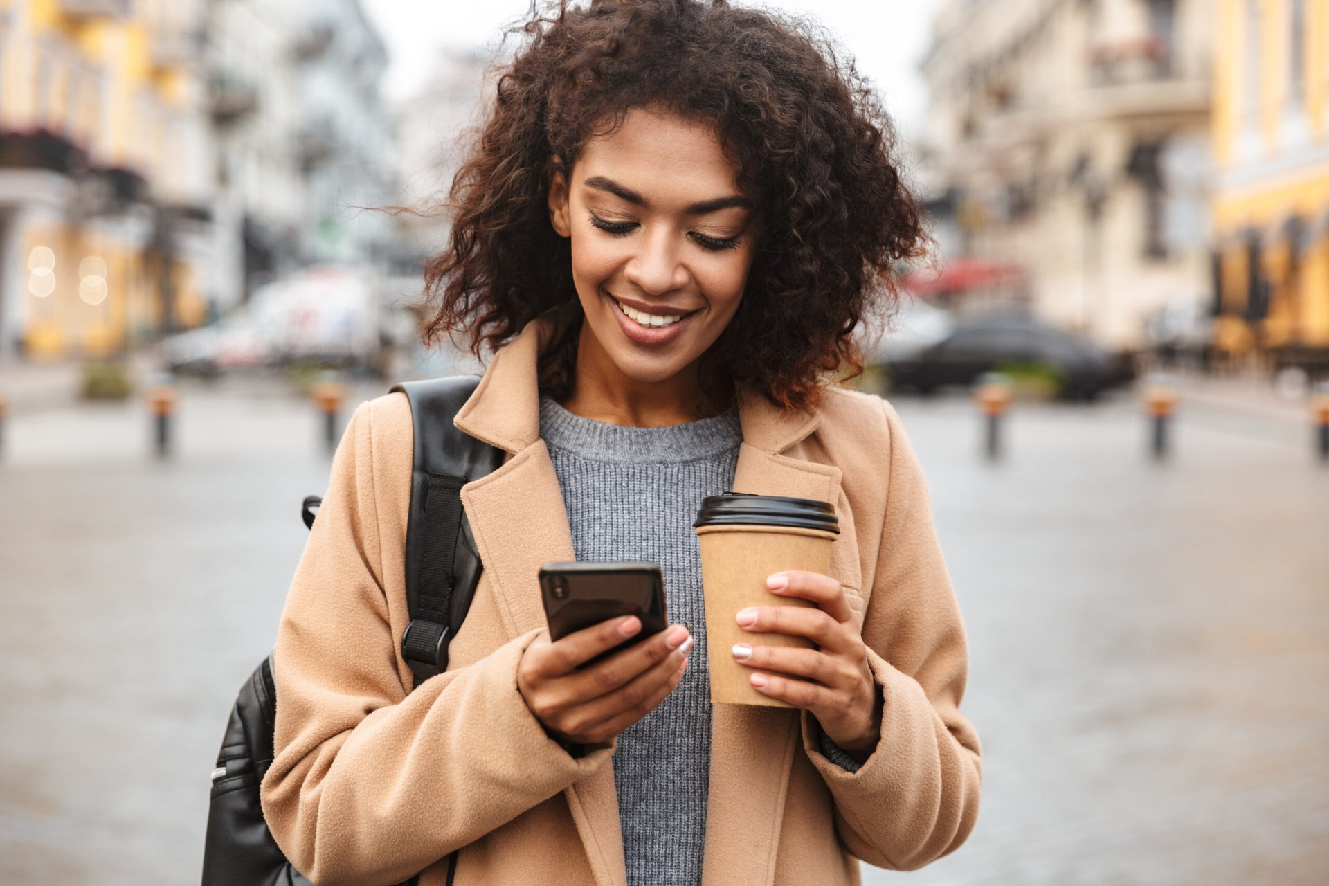 Happy woman walking with phone and coffee
