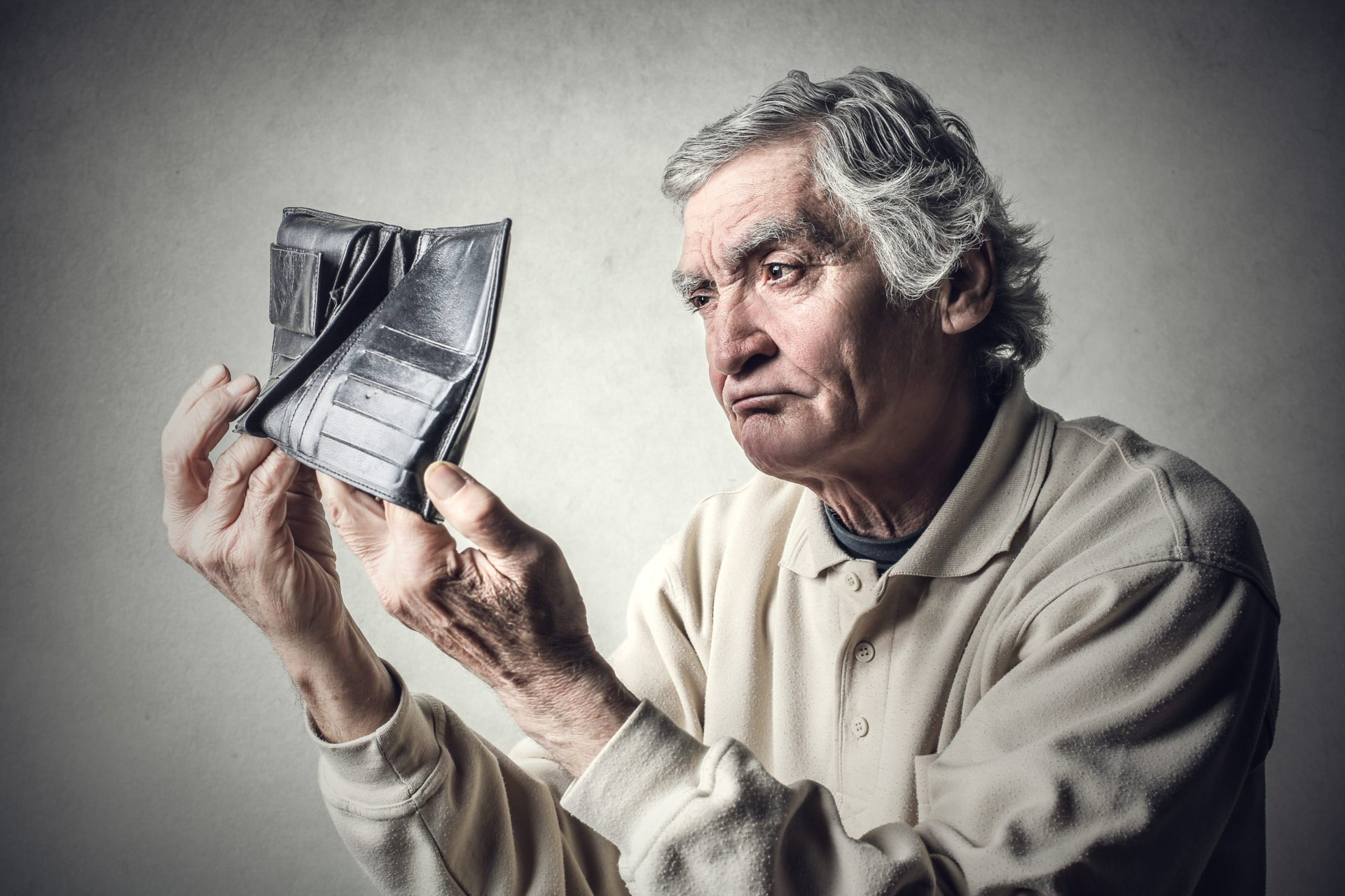 Broke senior holding an empty wallet