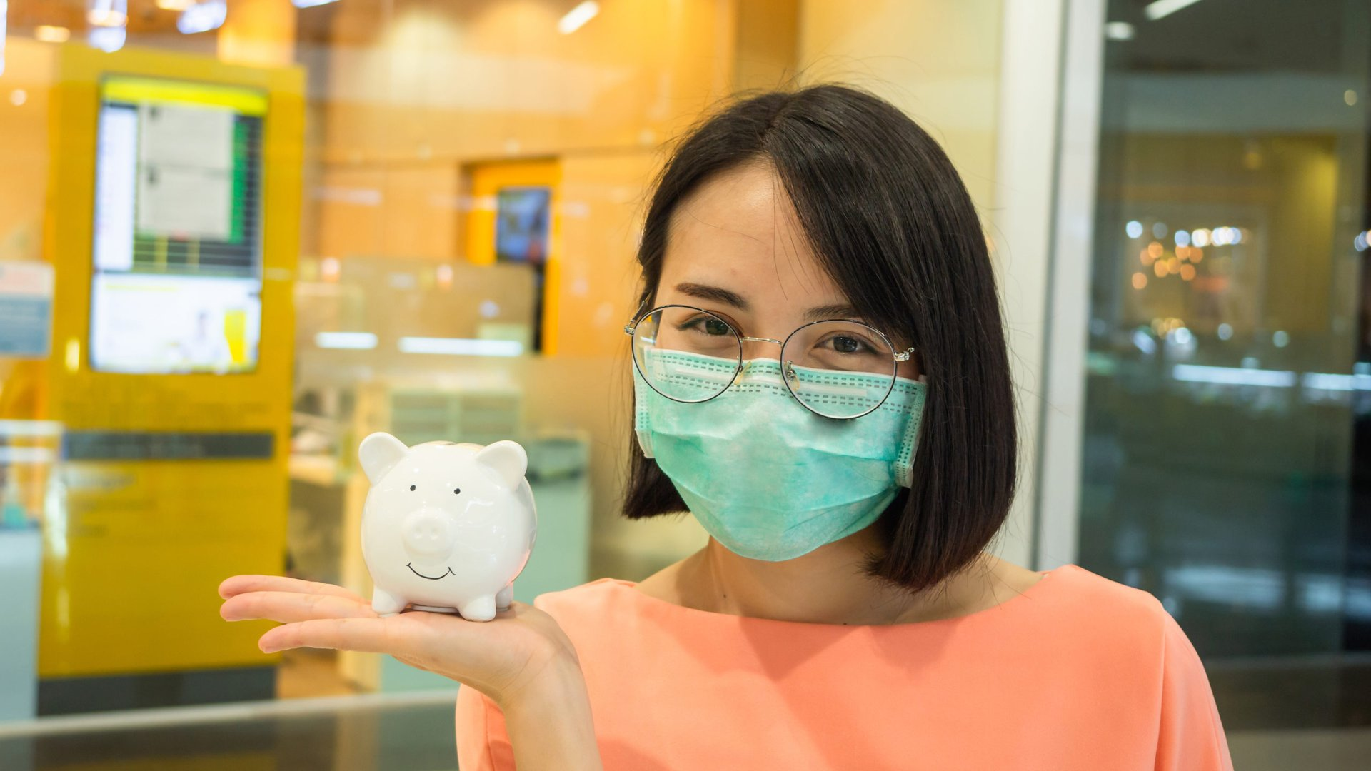 A woman in a mask holds a piggy bank at a bank