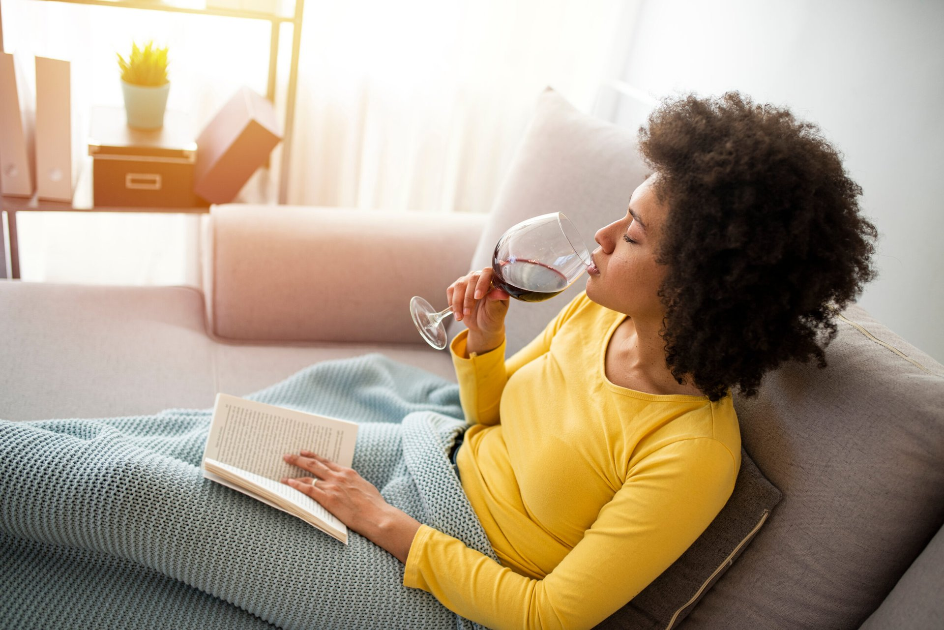 Woman drinking wine and reading a bookl