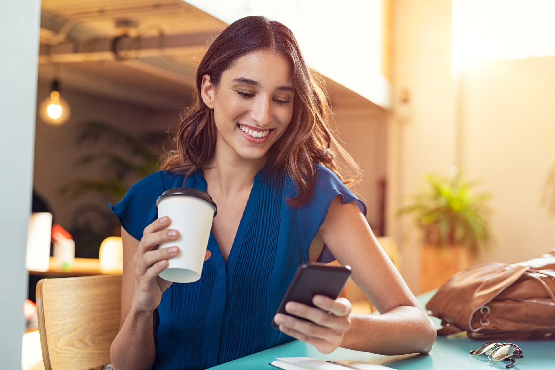Woman happy with her phone and a coffee