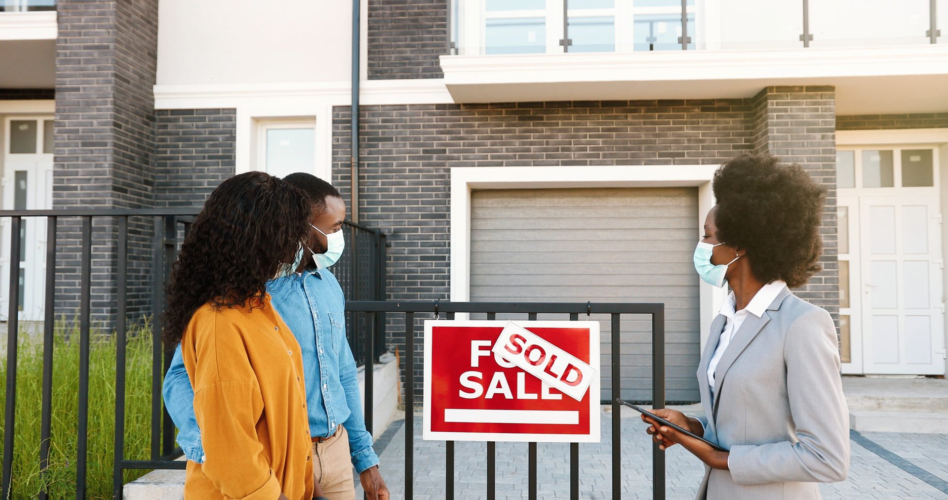 Homebuyers meeting a real estate agent at a property during the pandemic