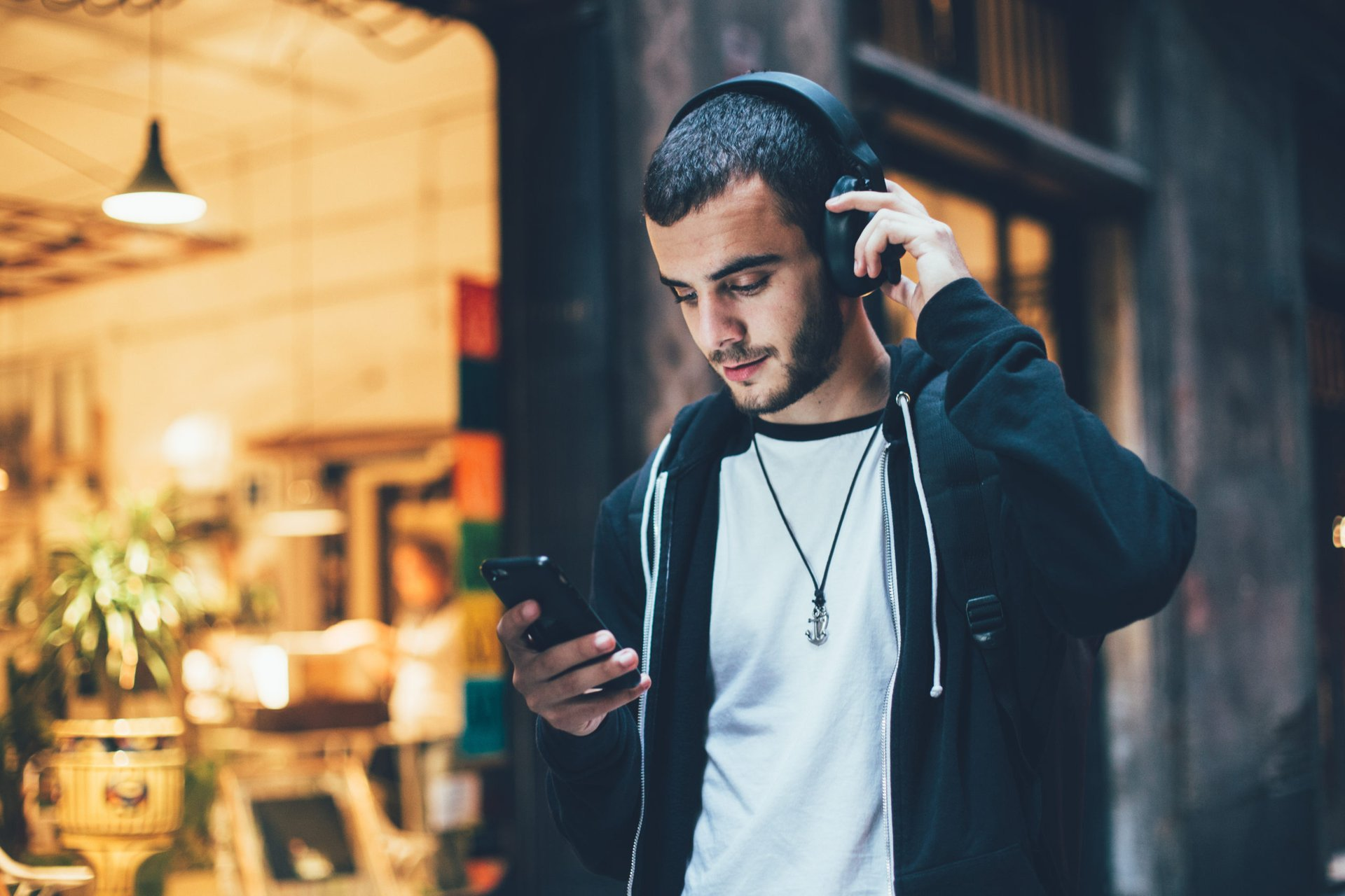 Young man wearing headphones and looking at his phone