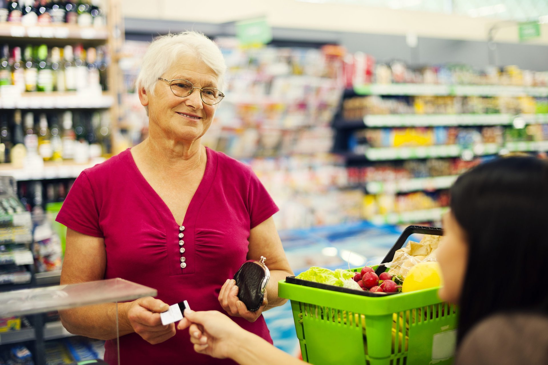 Senior woman earning grocery cash back rewards at the store