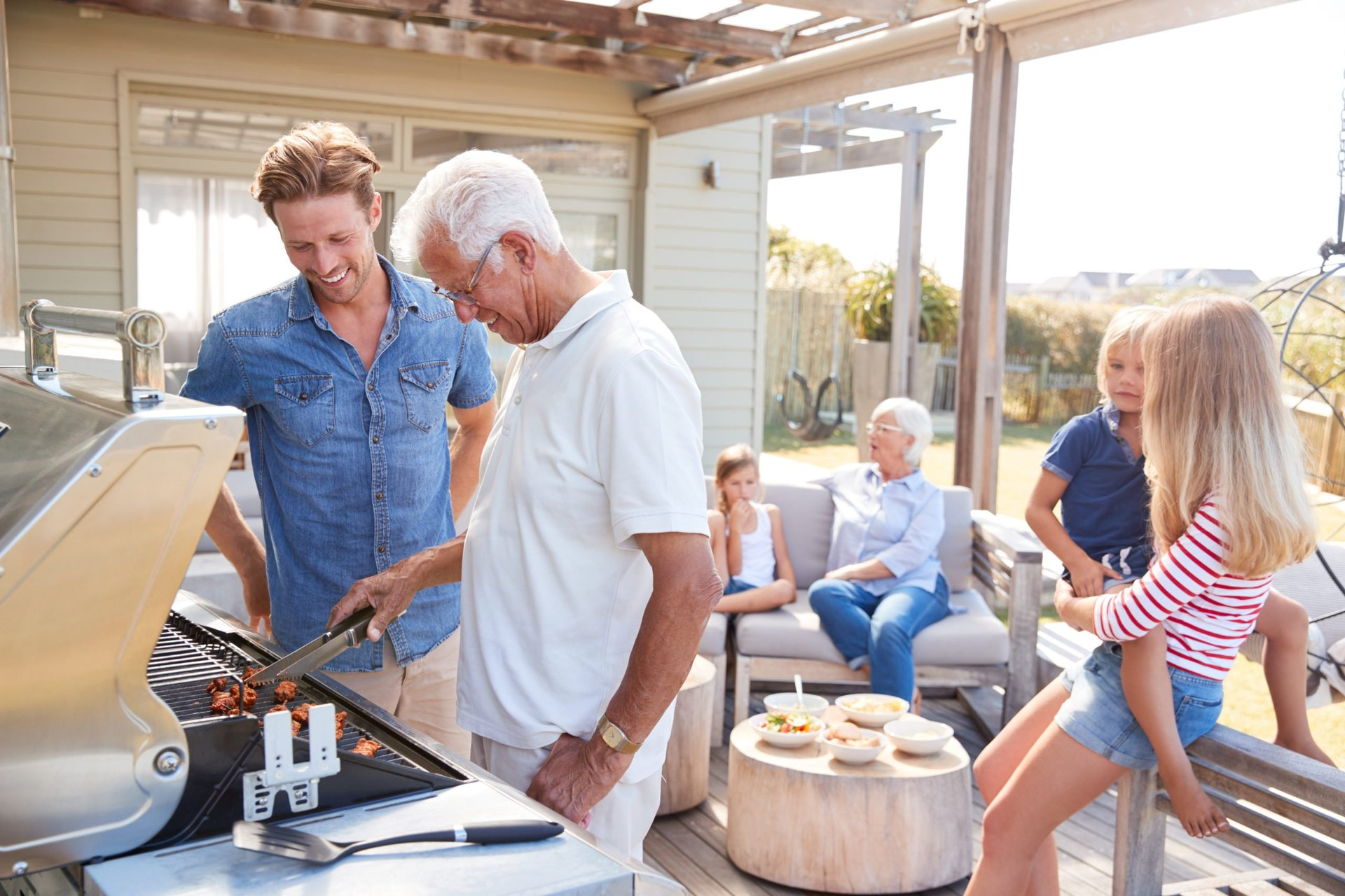 Family grilling on the deck of their home
