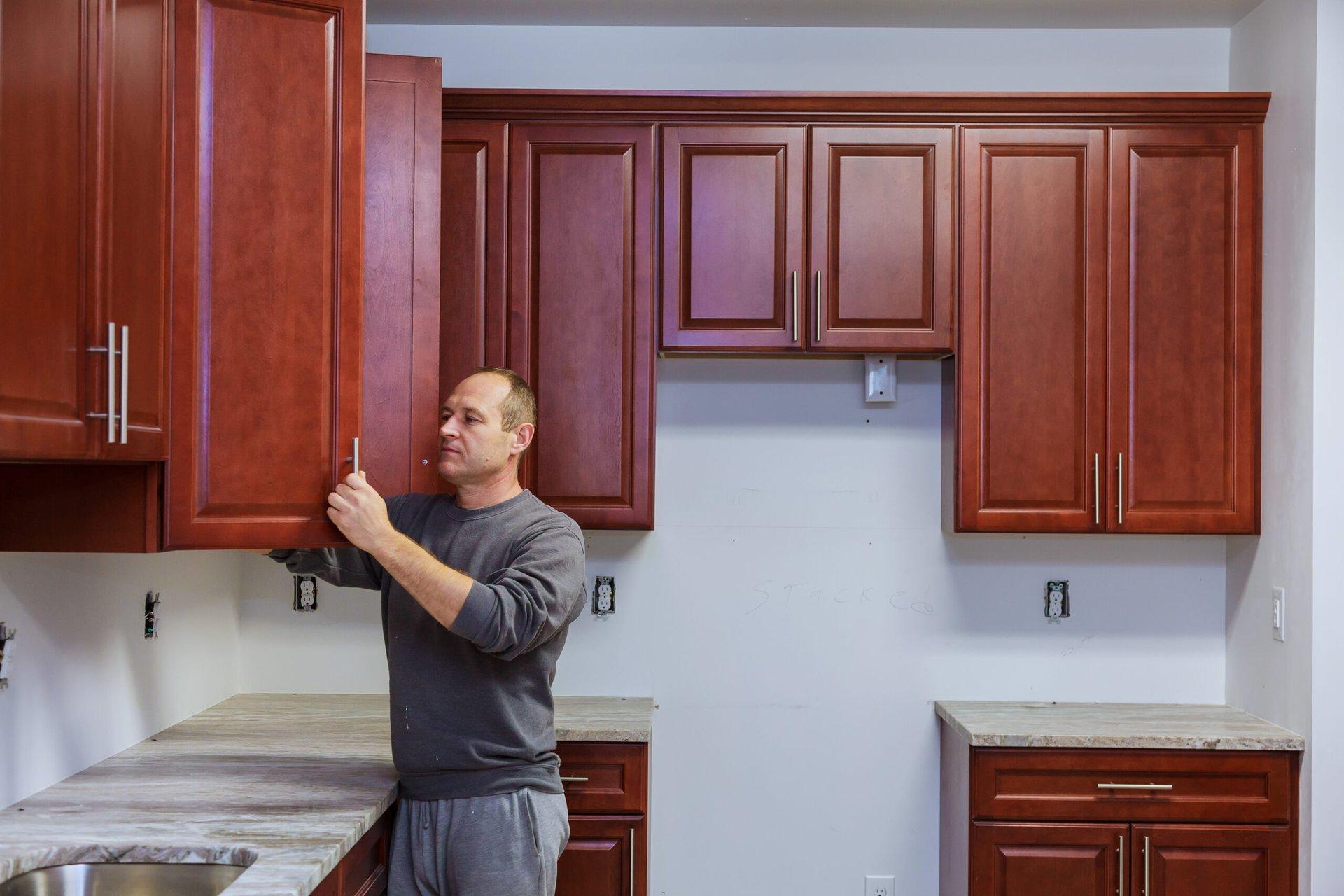 Carpenter putting in kitchen cabinets