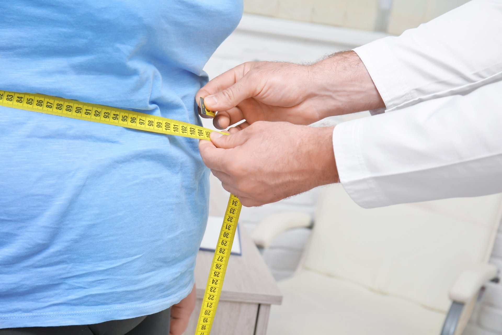 Doctor measuring waistline