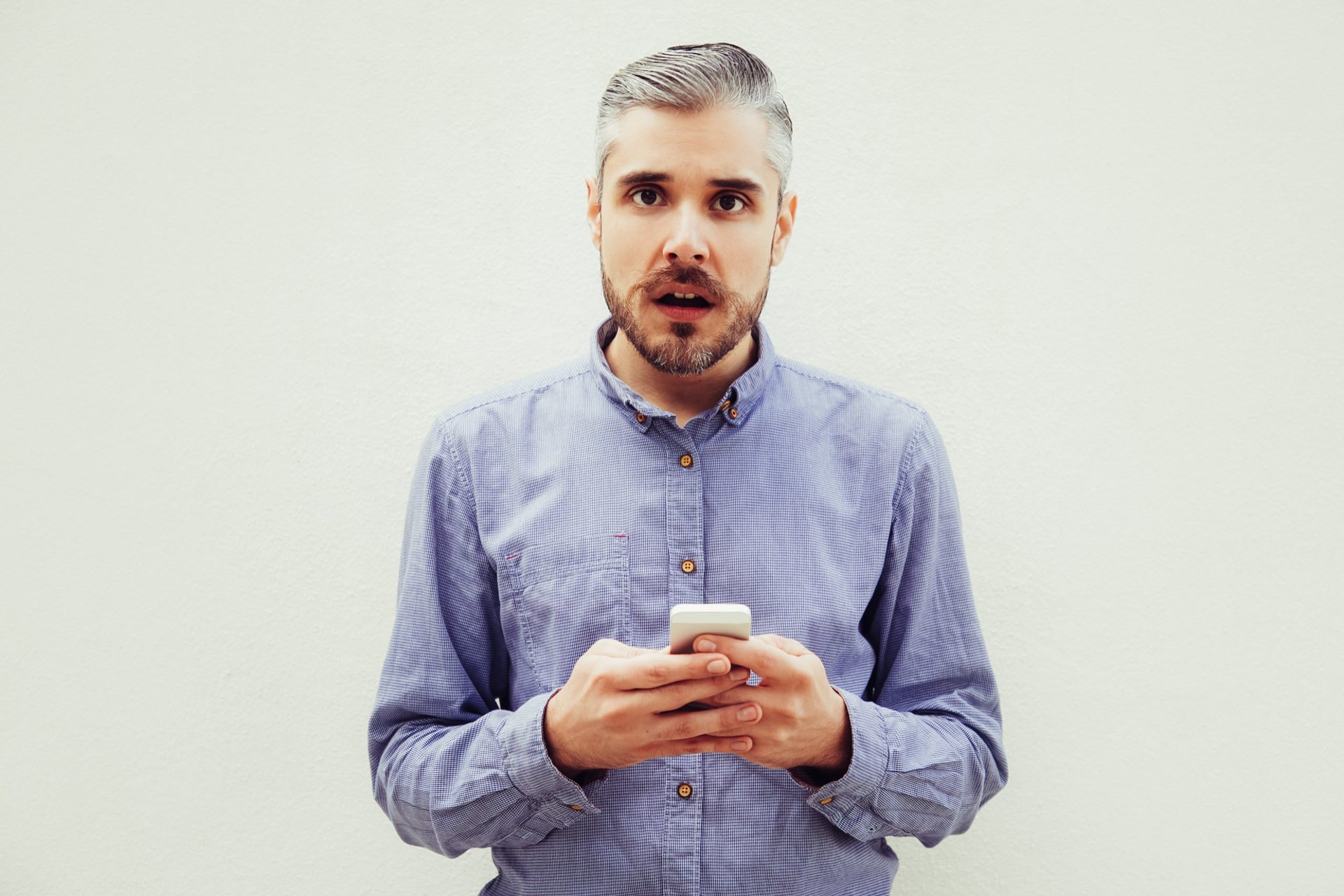 Man looks surprised by his cell phone