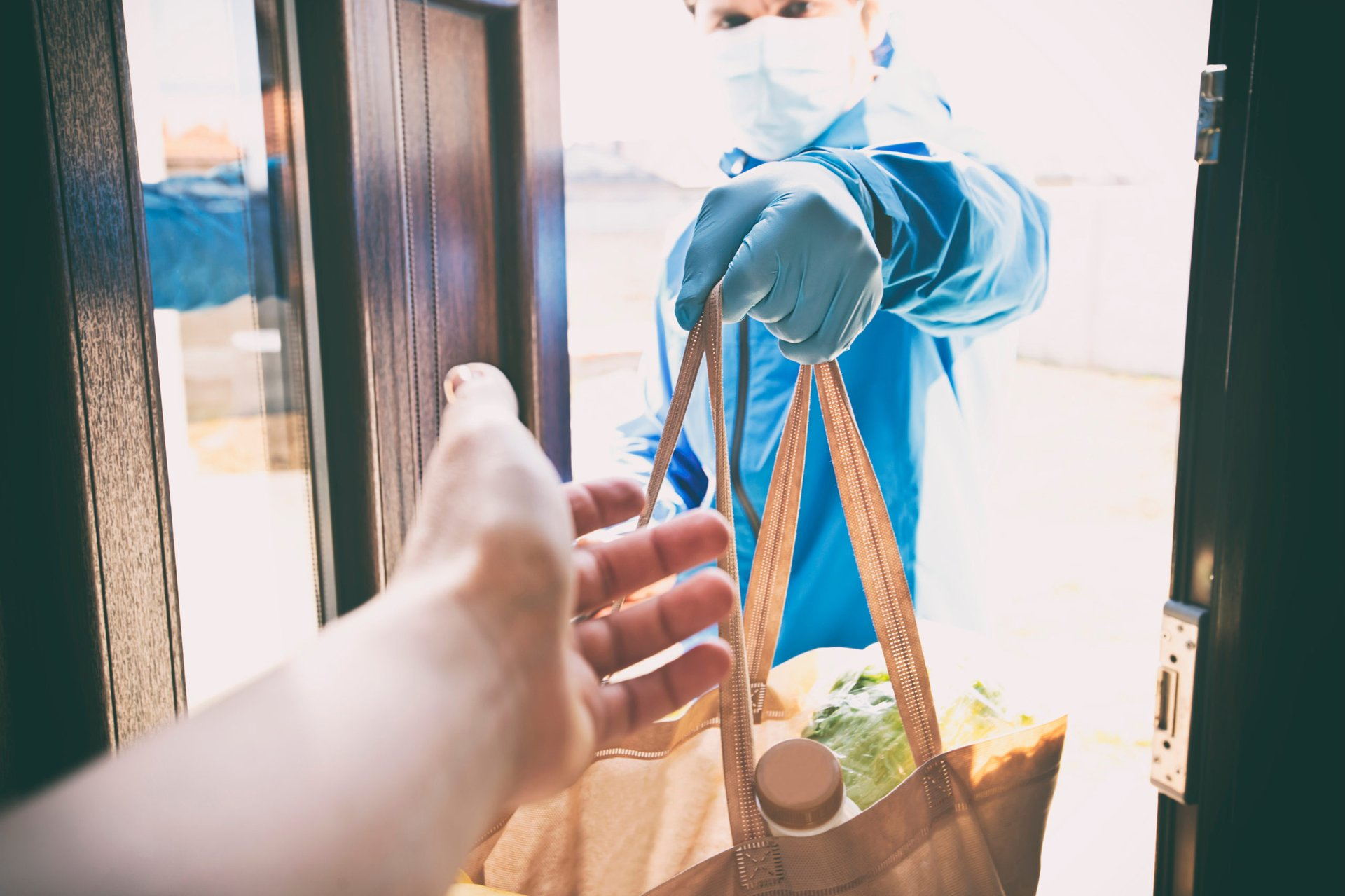 Grocery delivery mask handing bag of groceries