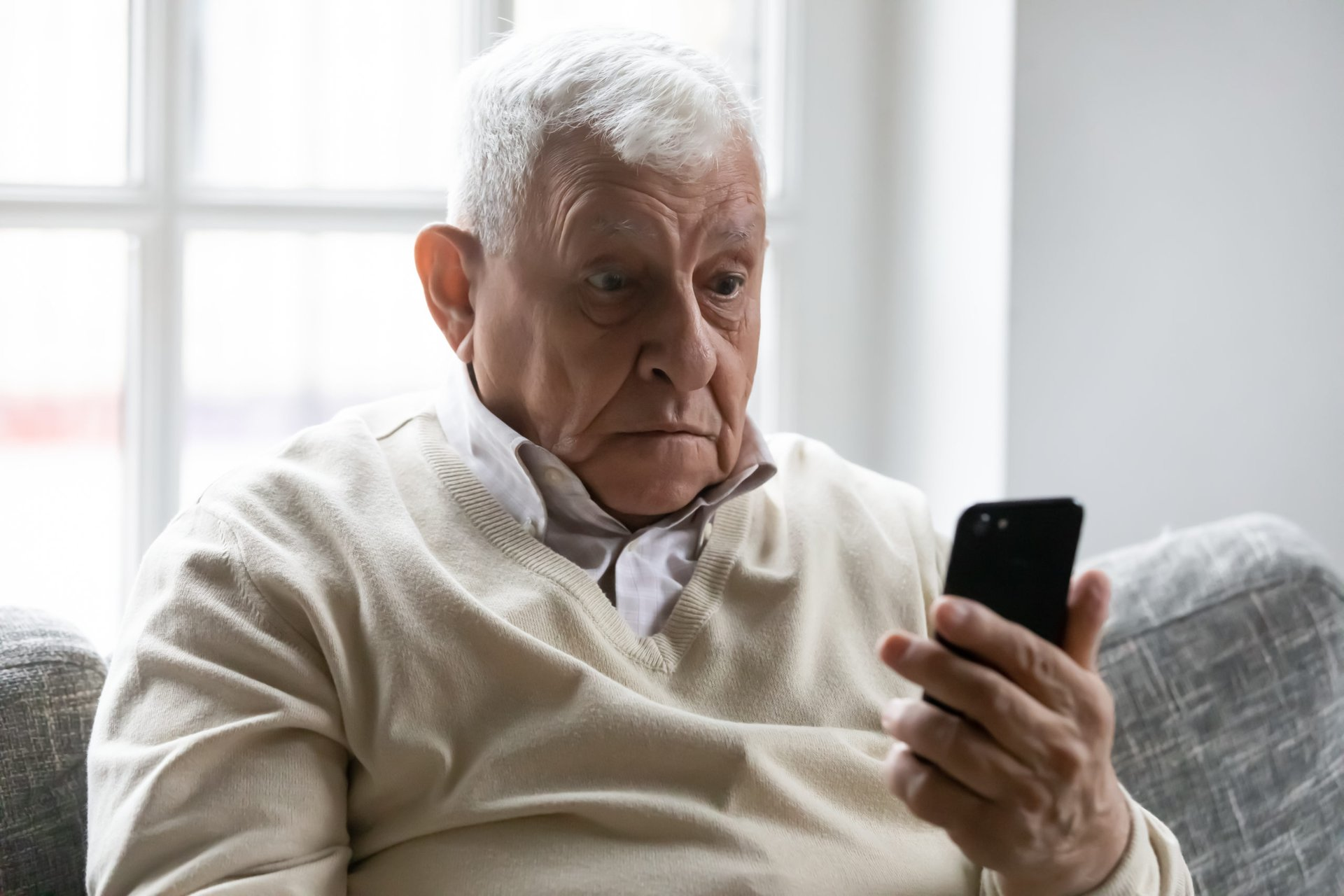 Surprised senior holding a smartphone