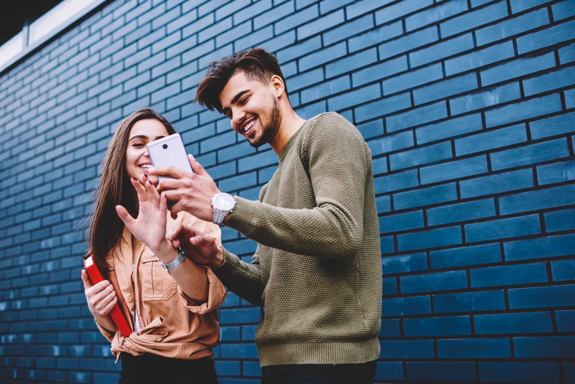 Young friends smiling at a smartphone video