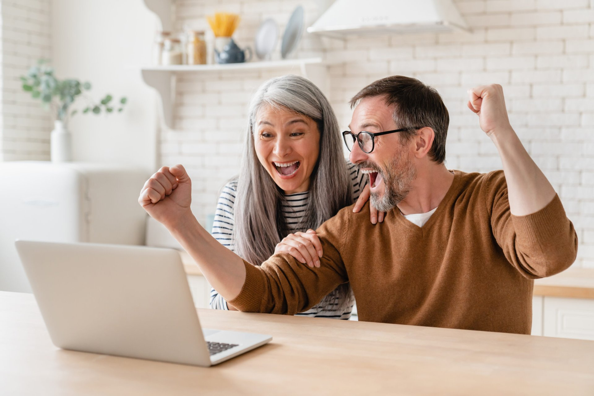 Excited homeowners on a laptop