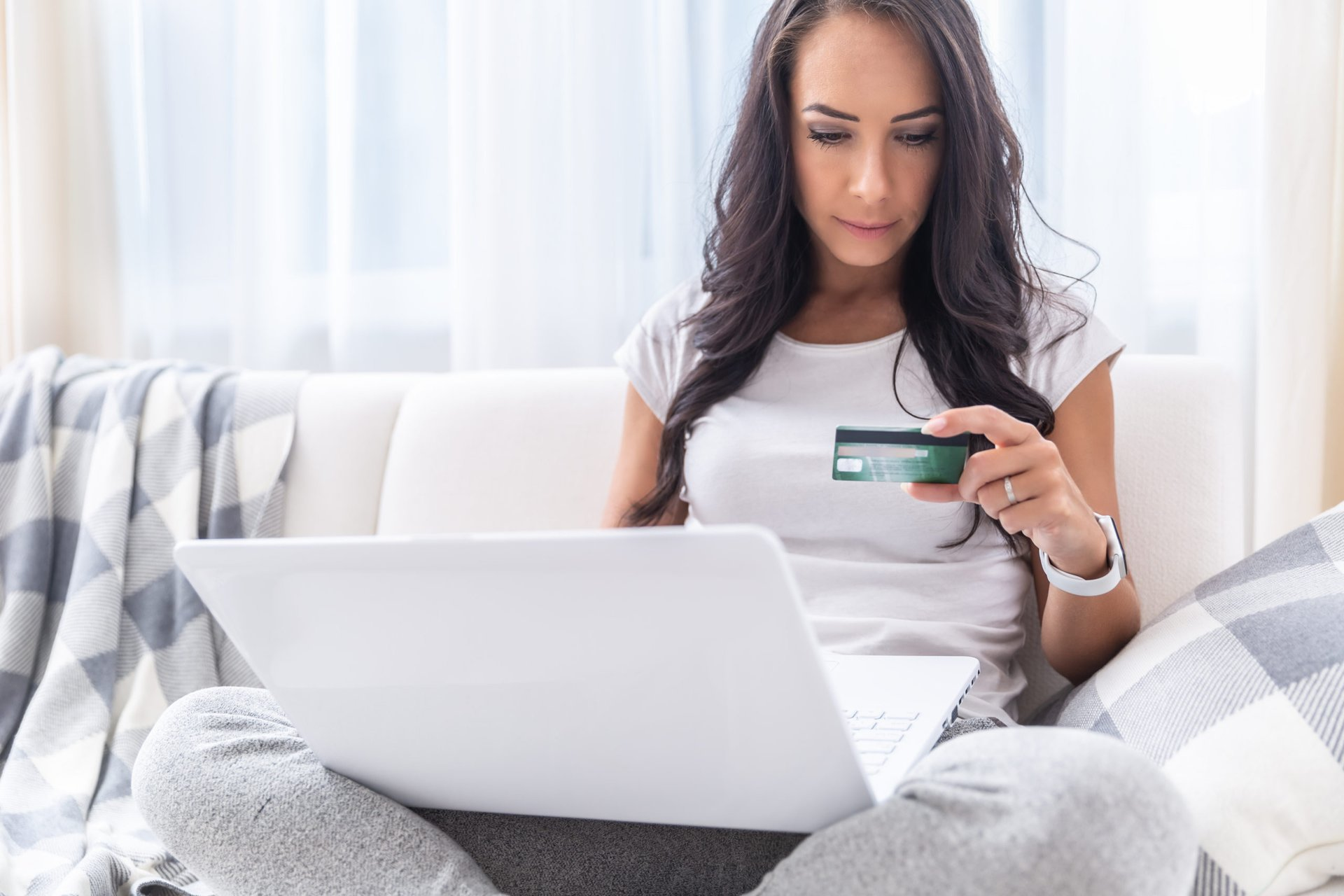 Young woman shopping with her rewards credit card online using her laptop