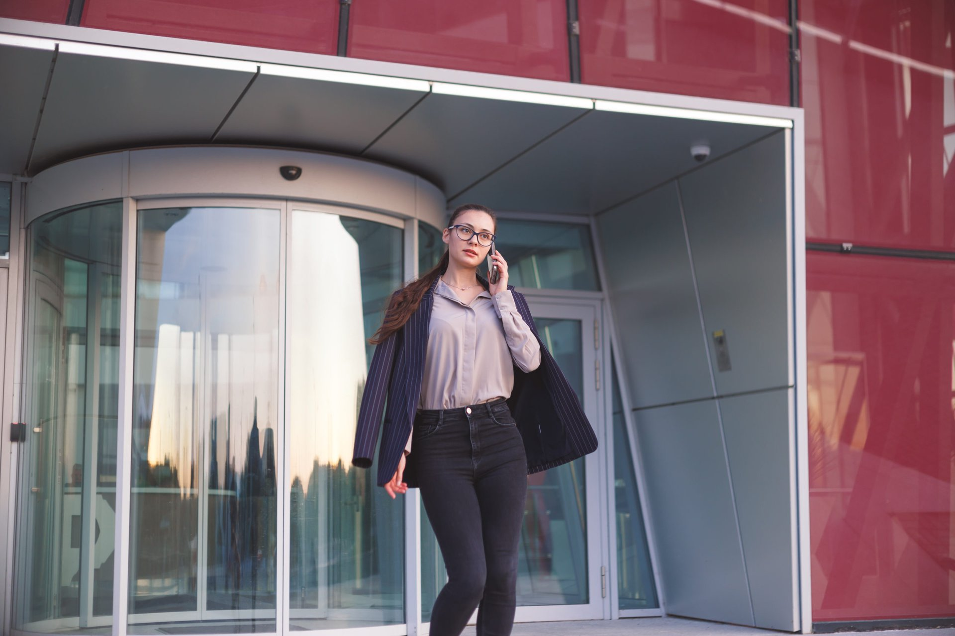 Businesswoman walking out of building on her phone