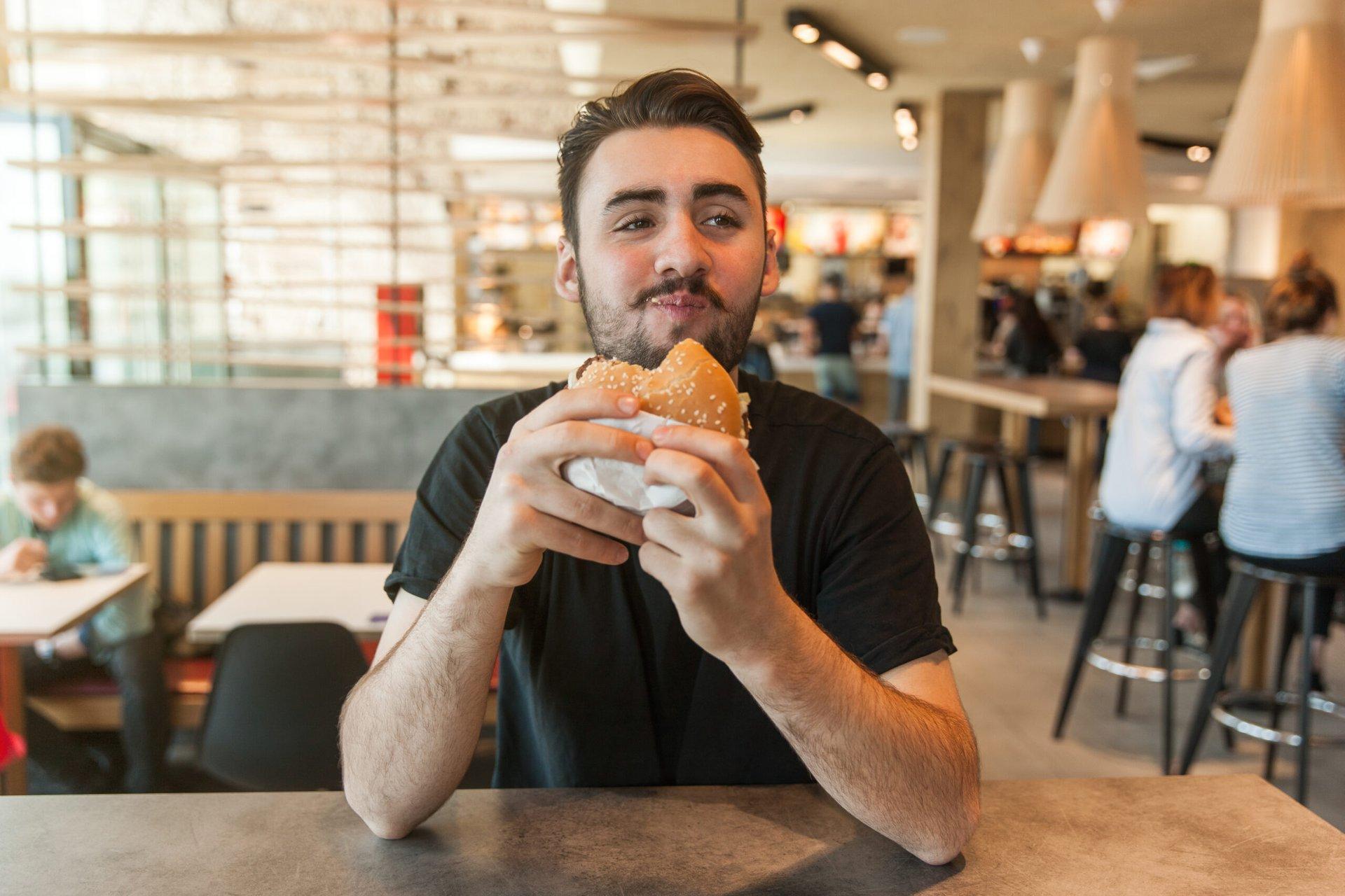 Man eating a burger at a restaurant