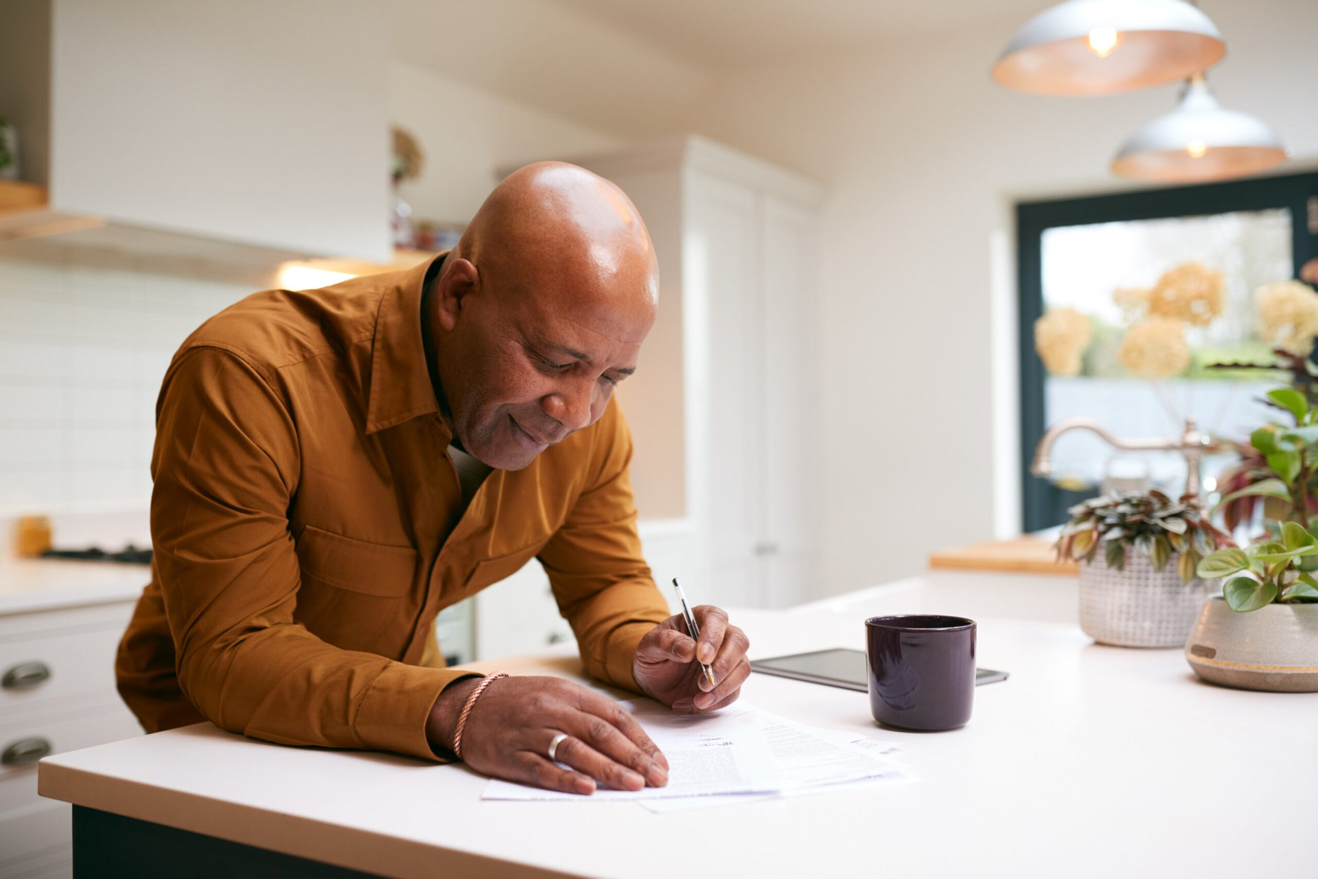 Retiree reviewing financial documents in his kitchen
