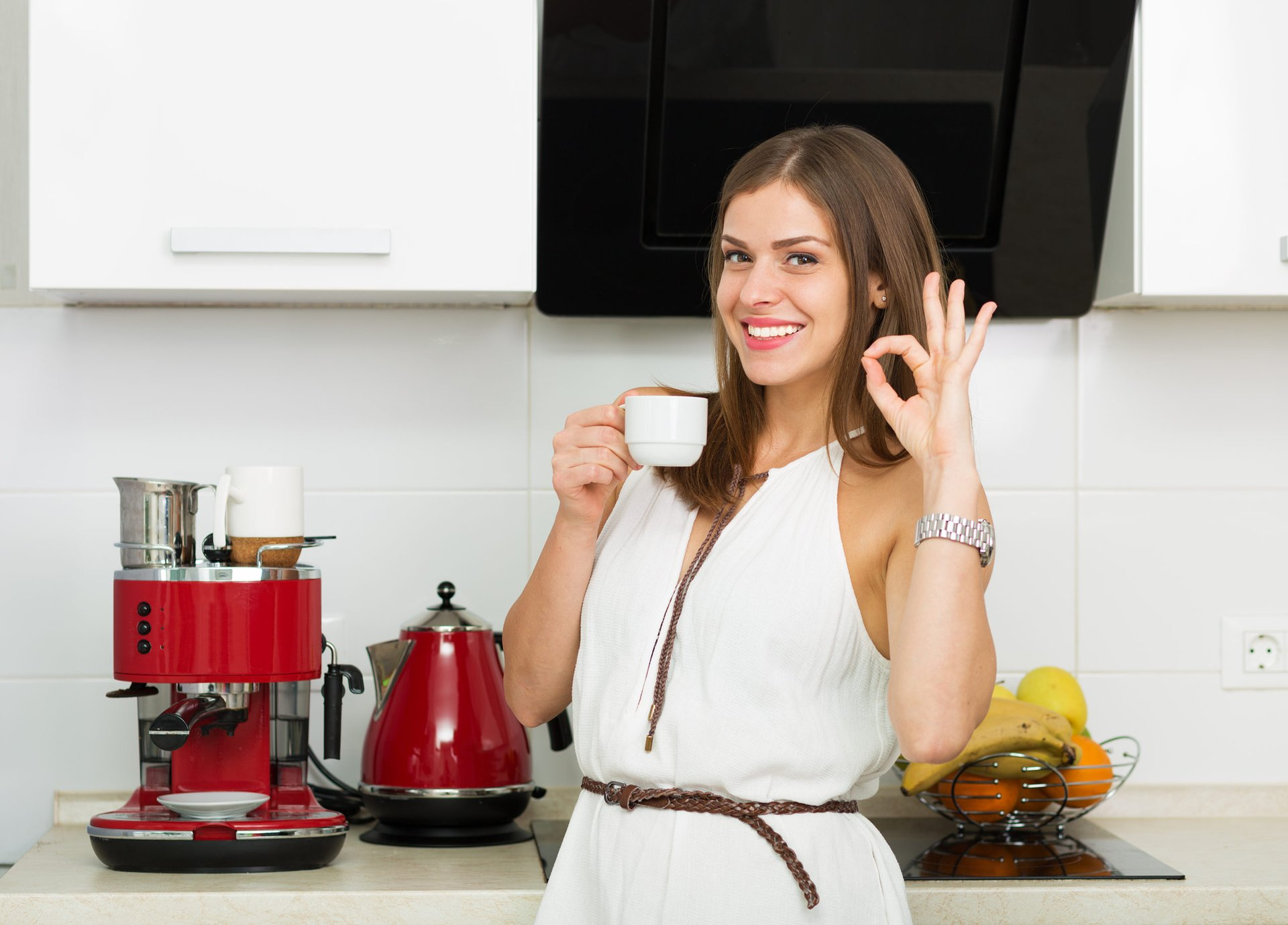 Woman drinking coffee in her kitchen