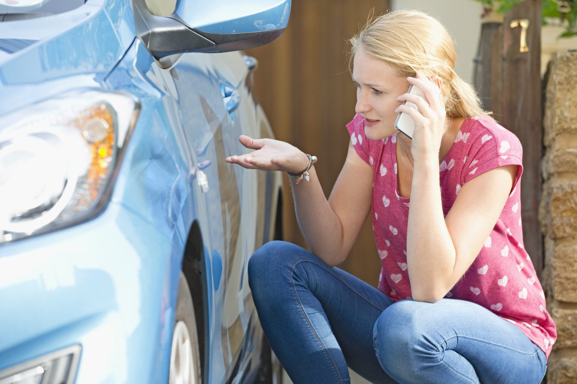 Woman on the phone reporting car damage to her insurance company