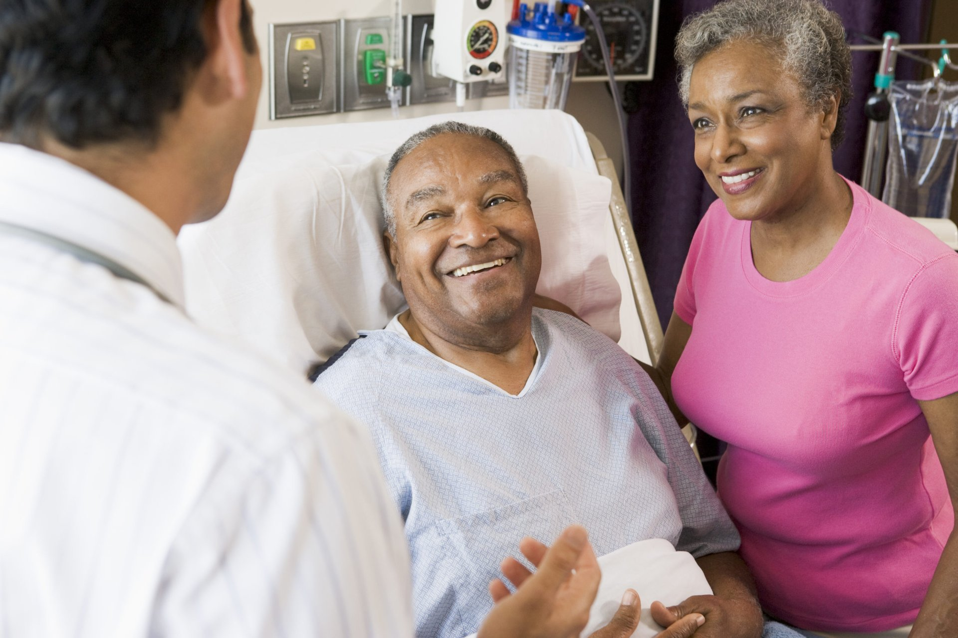 Senior couple talking to a doctor in the hospital
