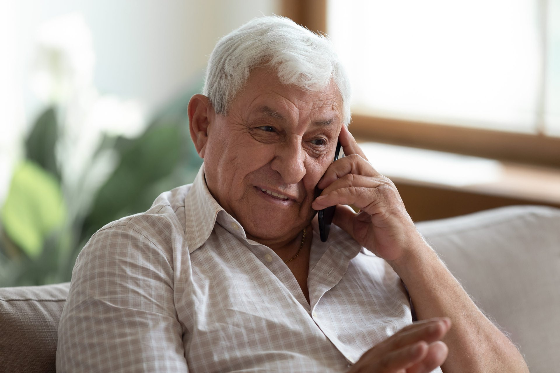Senior happily talking on smartphone or cellphone