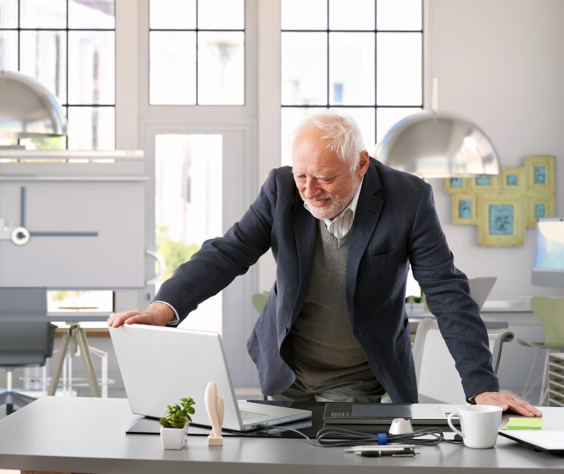 A senior worker checking his laptop