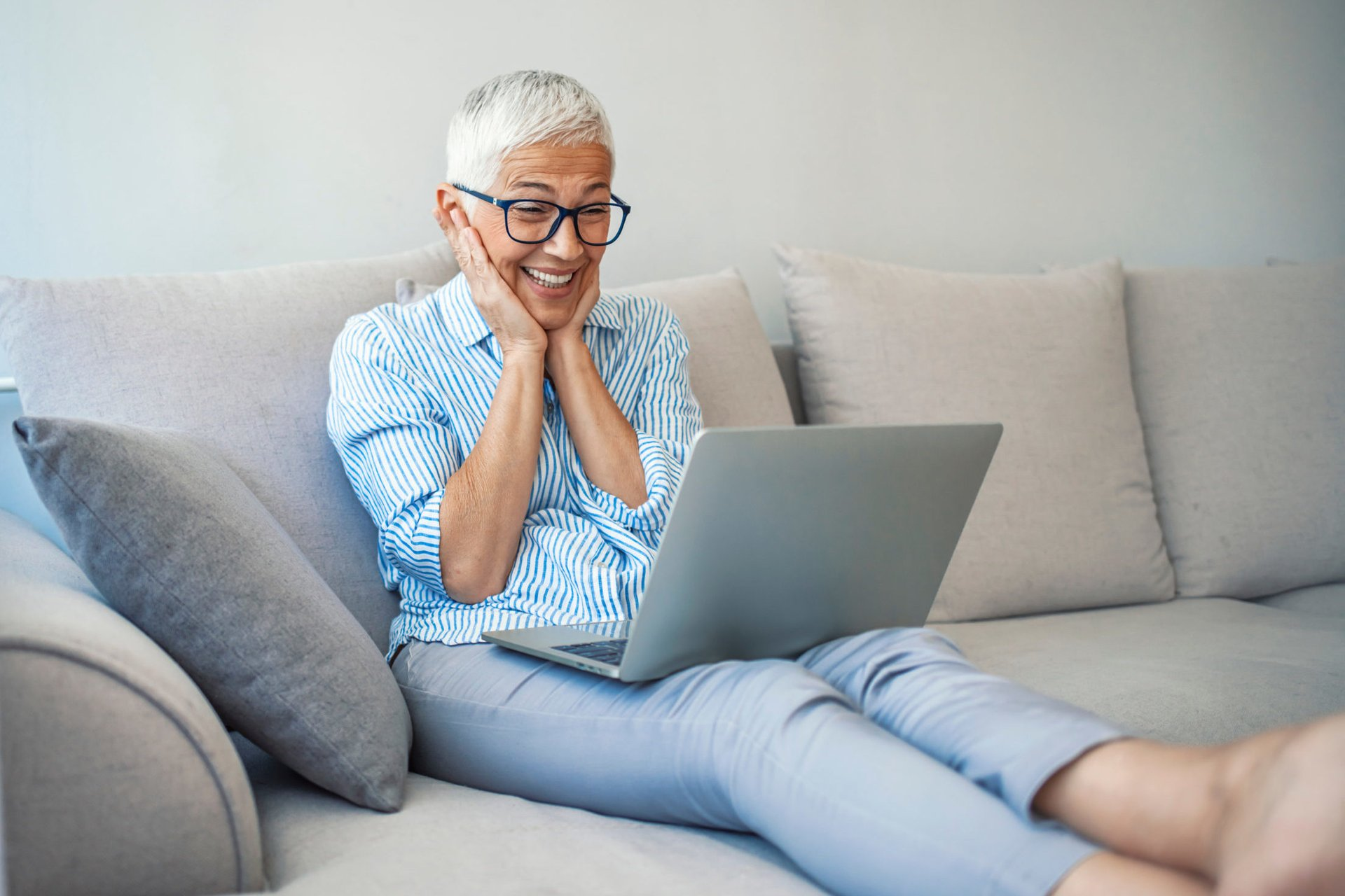 Excited senior using a laptop